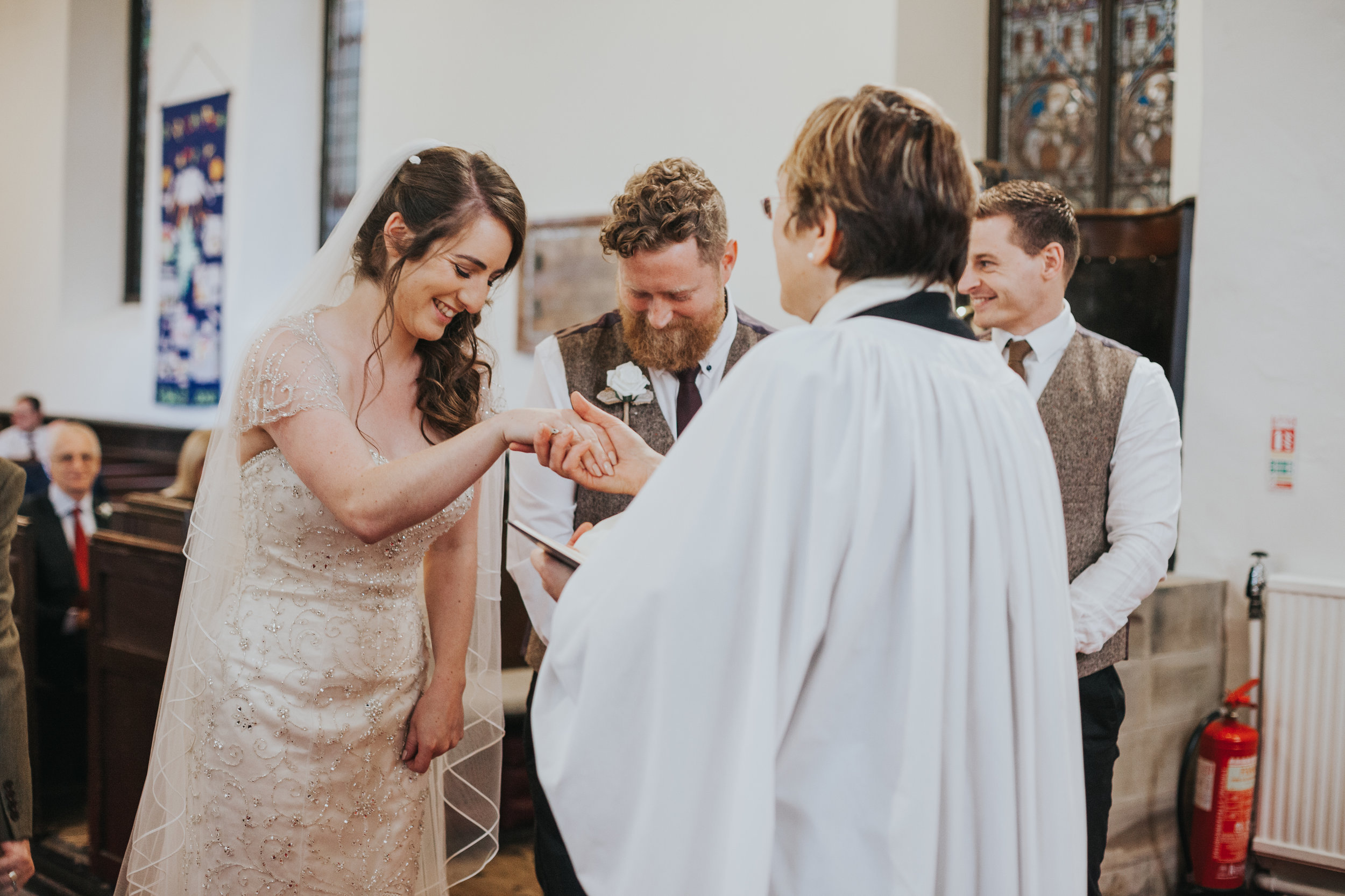 Female vicar holds bride's hand. Bride laughs.