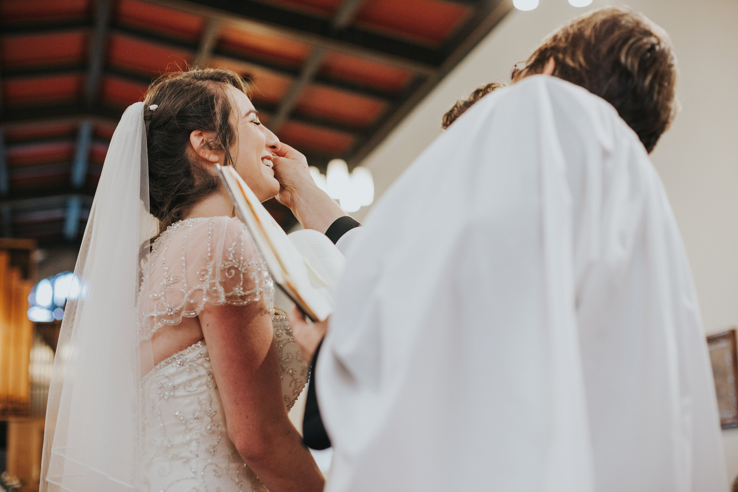 Female vicar wipes tears from brides face, while bride laughs.