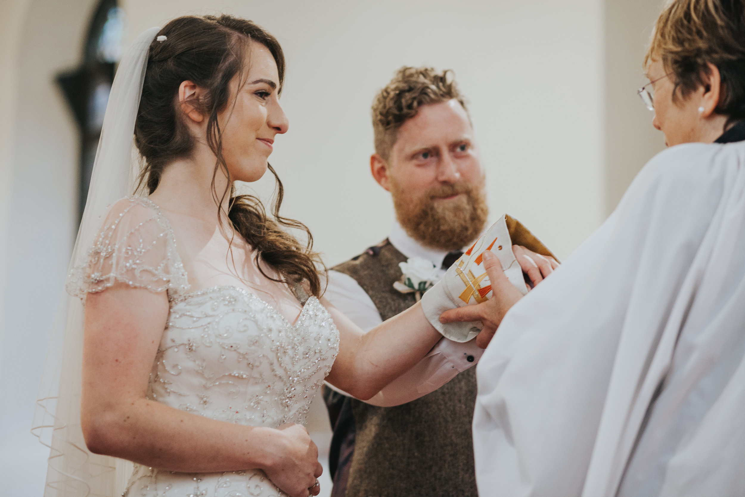 Vicar wraps couples hands in fabric.