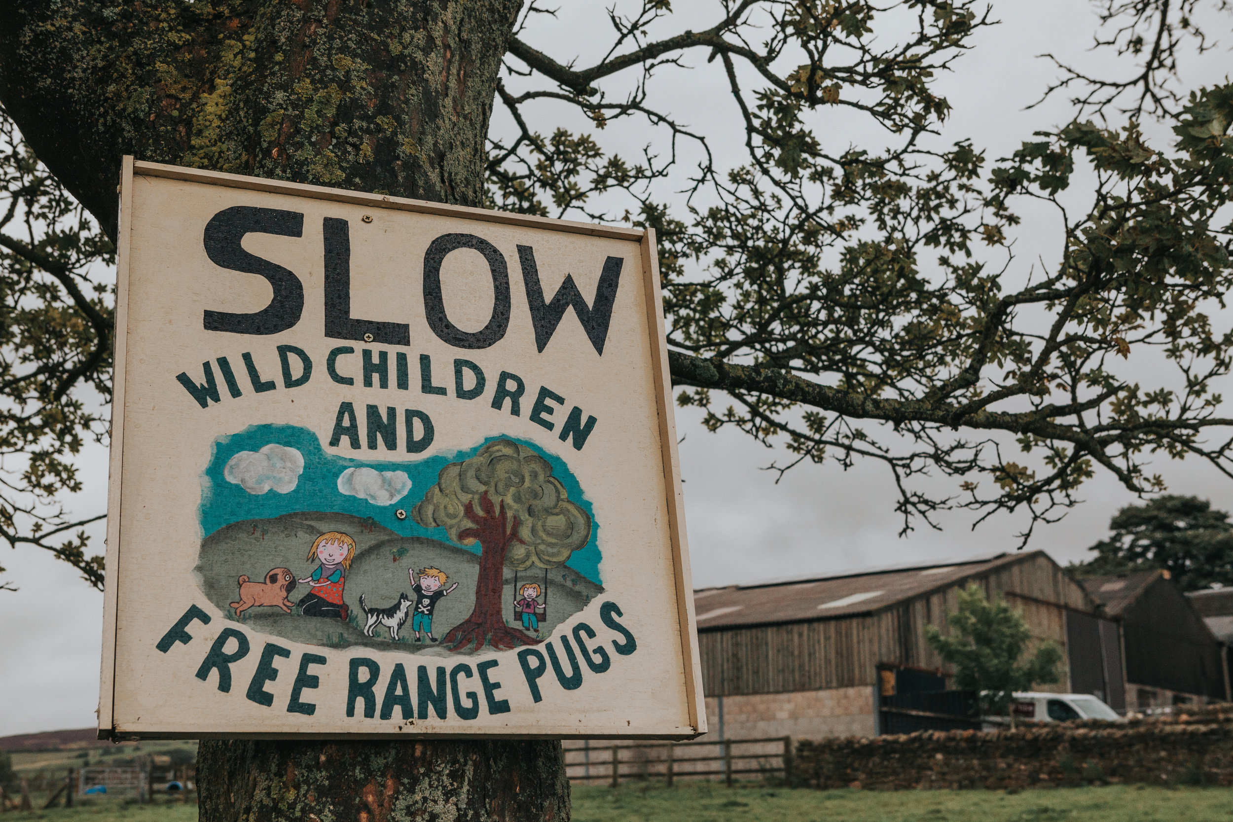 "Sign reads ""SLOW WILD CHILDREN AND FREE RANGE PUGS"" We have arrived at Thornsett Field Farm it seems."