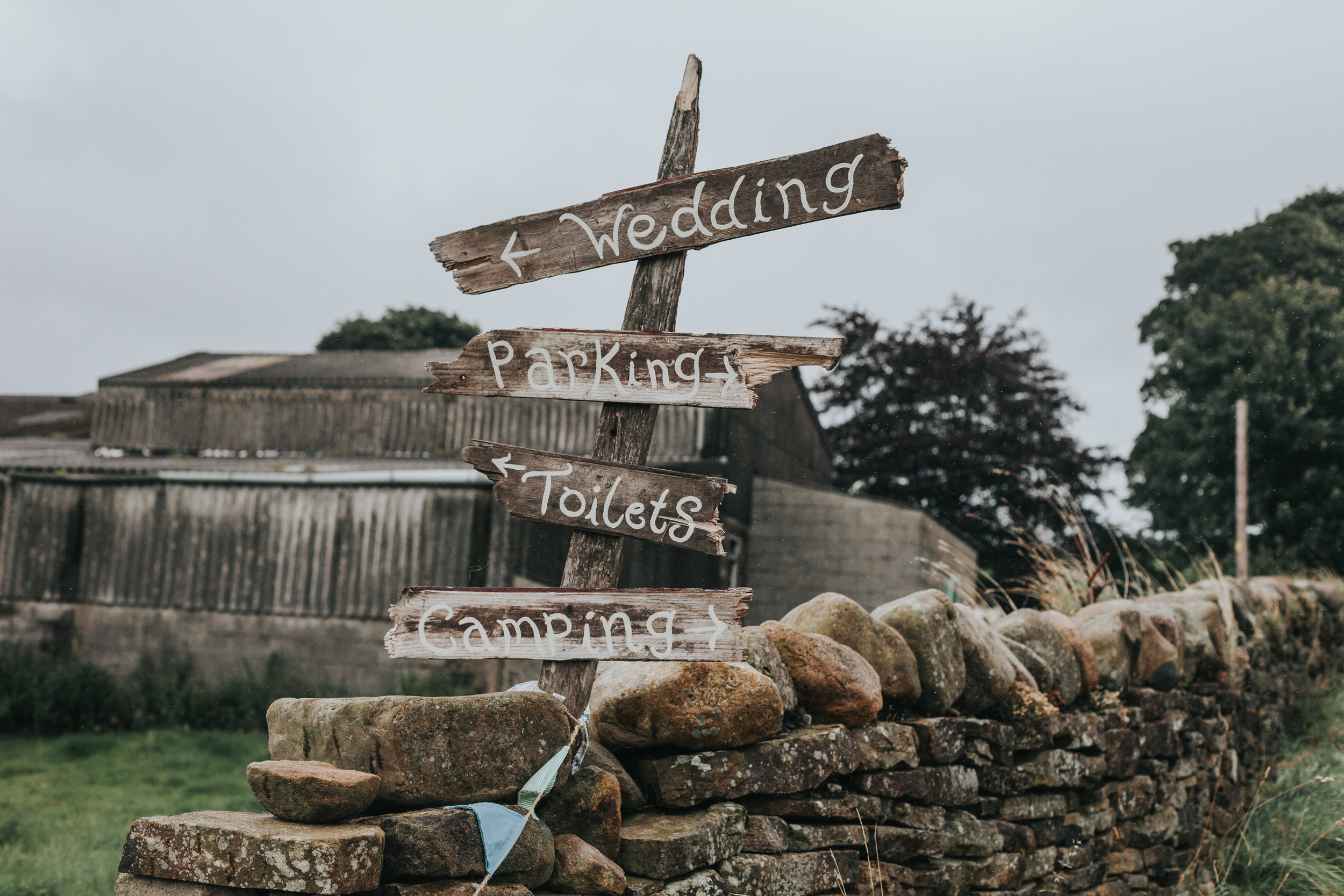 Hand made signs on wood reading WEDDING, PARKING, TOILETS AND CAMPING.