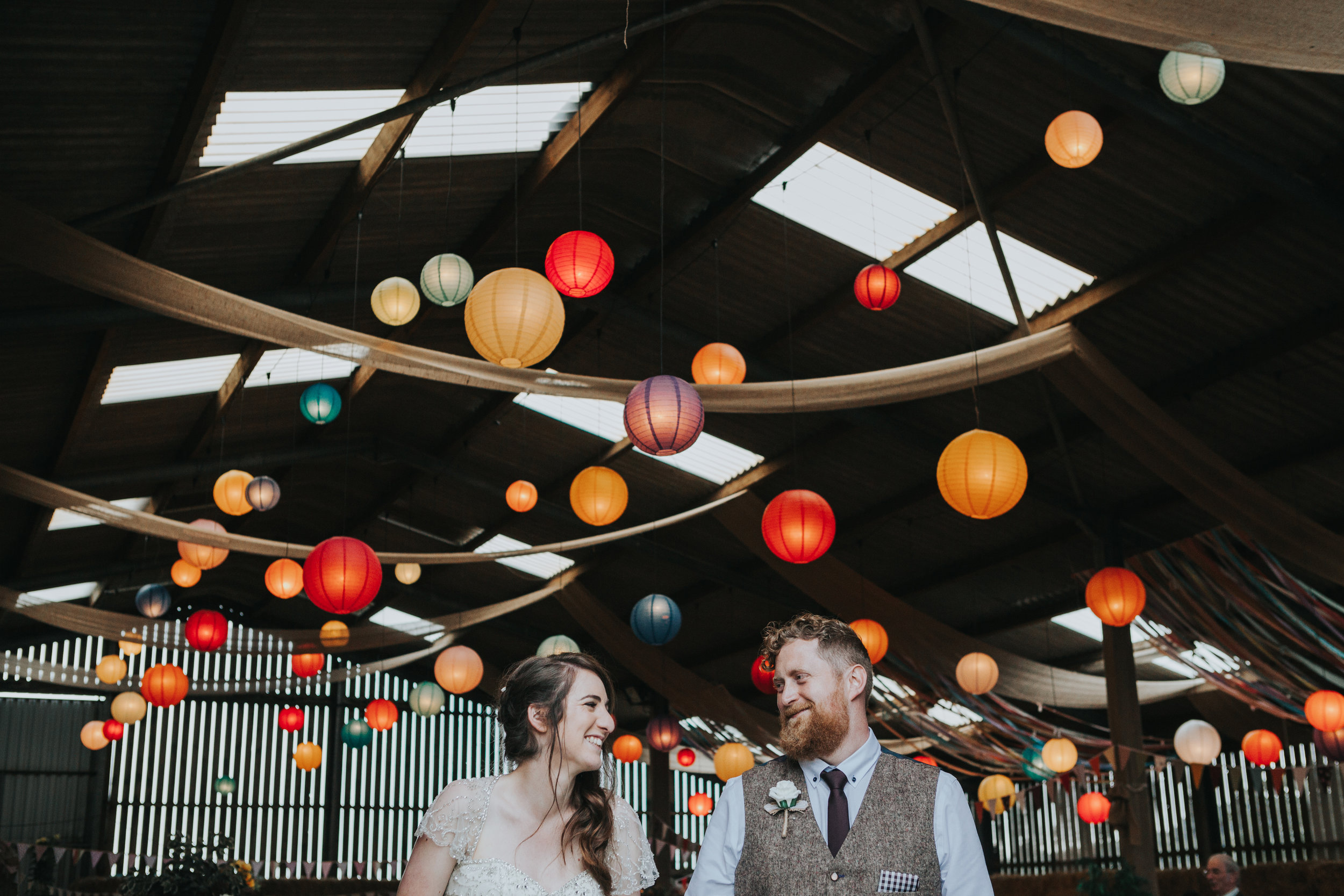 Bride and Groom stand together in front of room full of colourful lanterns that they put there together the day before