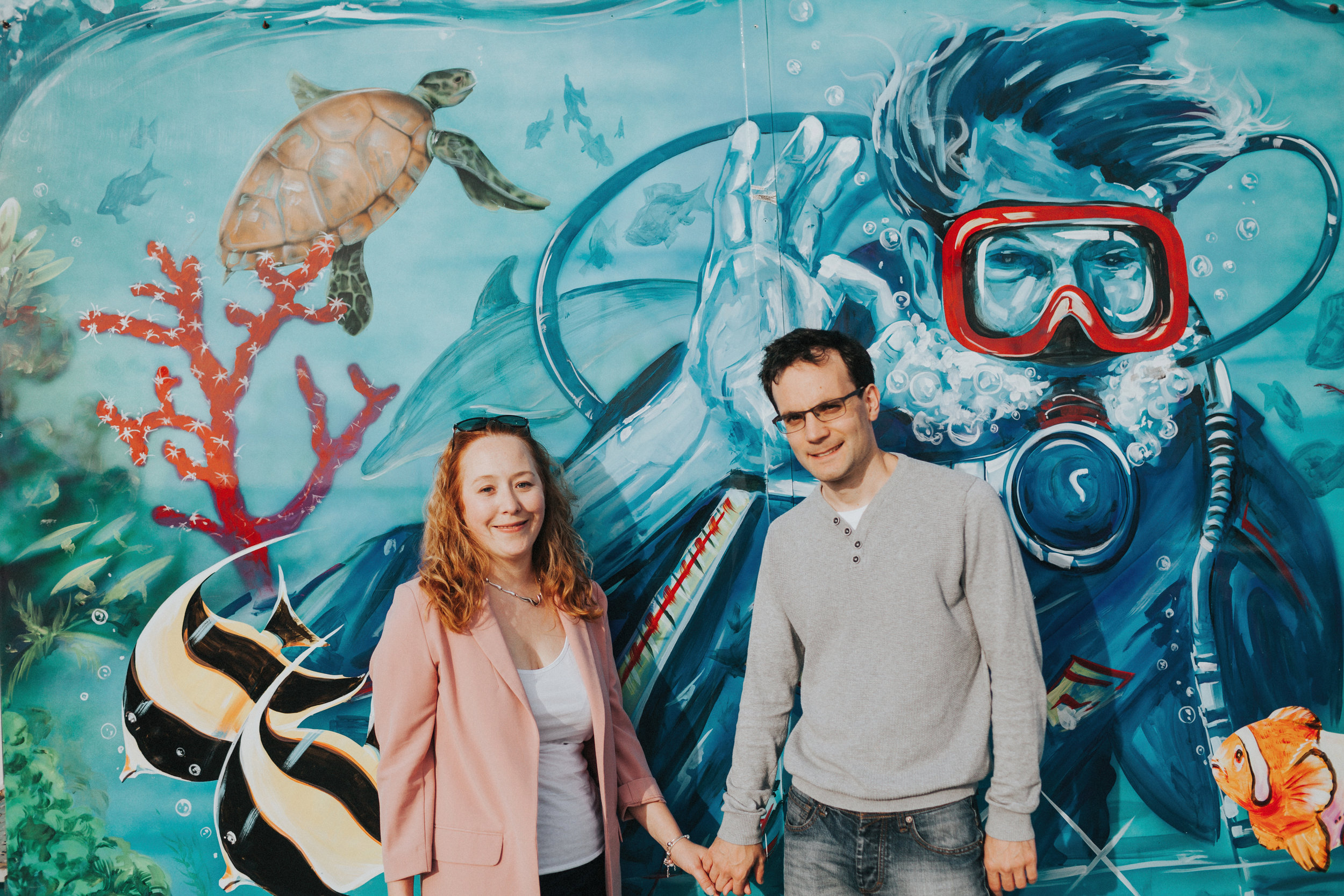 Couple in front of mural of divers in the River Mersey?