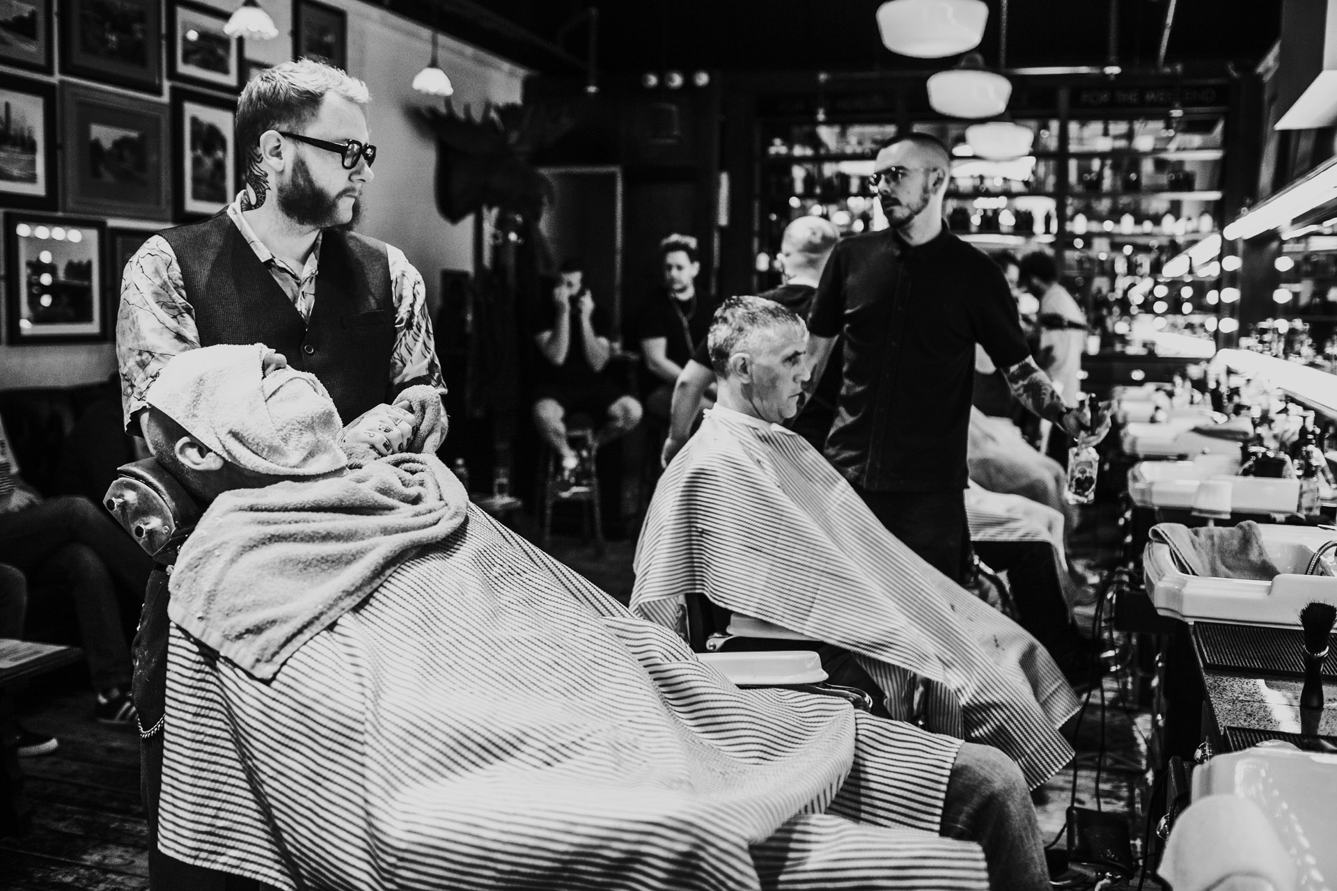 Grooms men getting cut throat shaves in Manchester wedding documentary style photographs