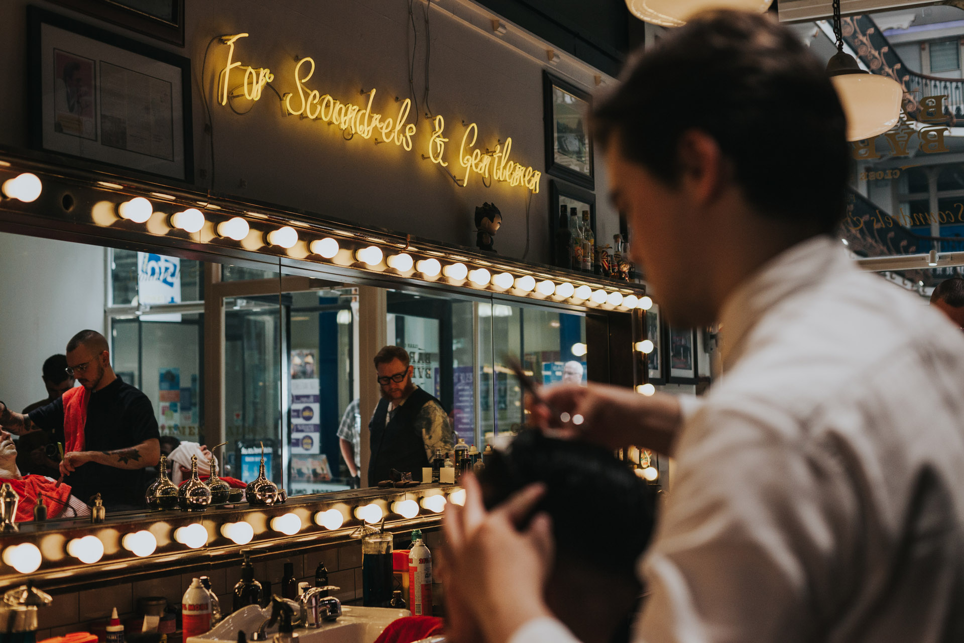 Barber and Groom in forground with neon sign in focus in the back ground