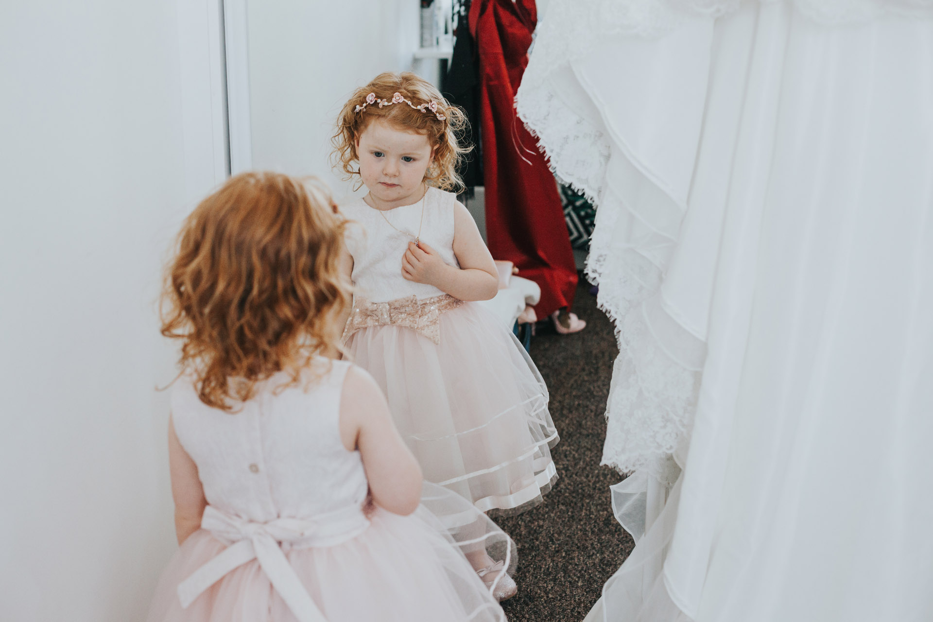 Flower girl looks at her self in the mirror in her special dress.