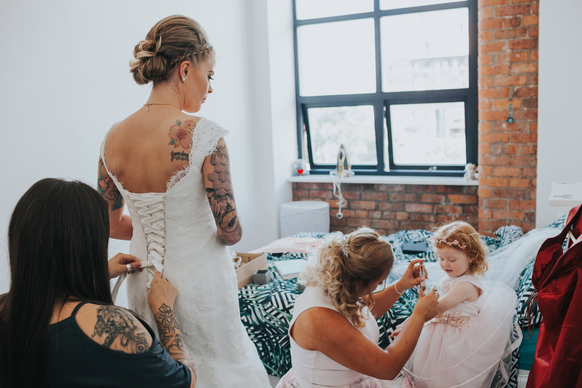 Bride has the back of her wedding dress fastened as bridesmaid puts make up on flower girl.