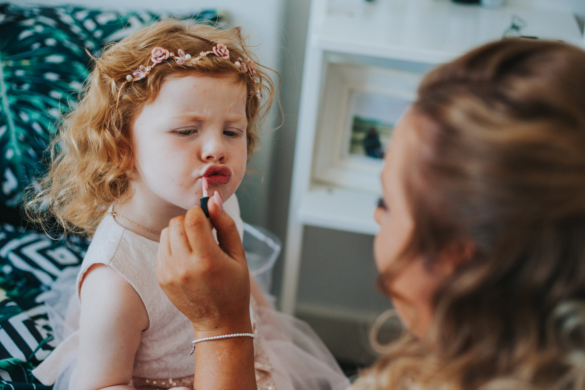 Flower girl pulls a funny pouty face as the bridesmaid puts lipstick on her.