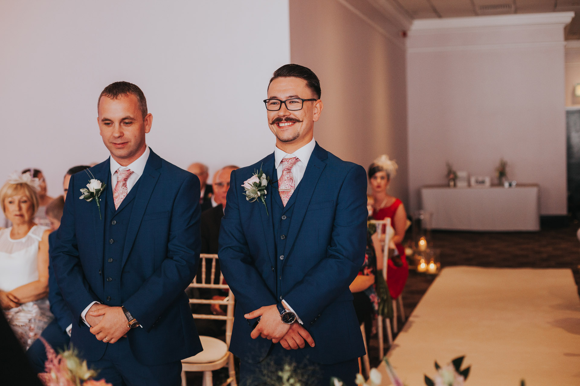Groom awaits bride smiling.