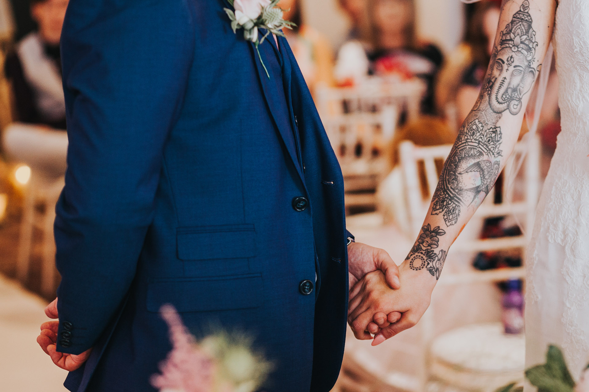 Brides beautiful tattooed arm stretches out to hold grooms hand. Close up photograph.