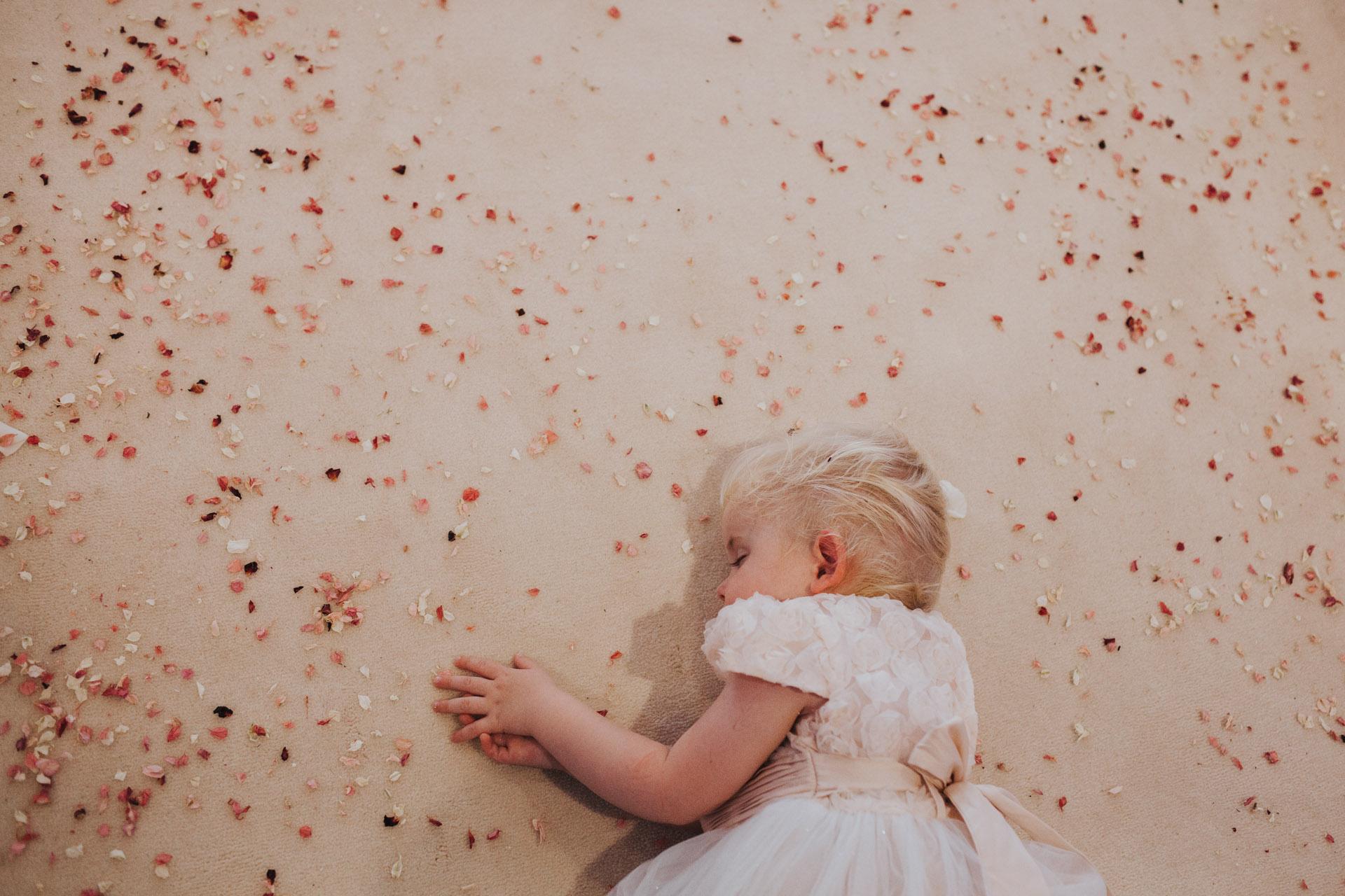 flower girl sleeps on confetti covered floor.