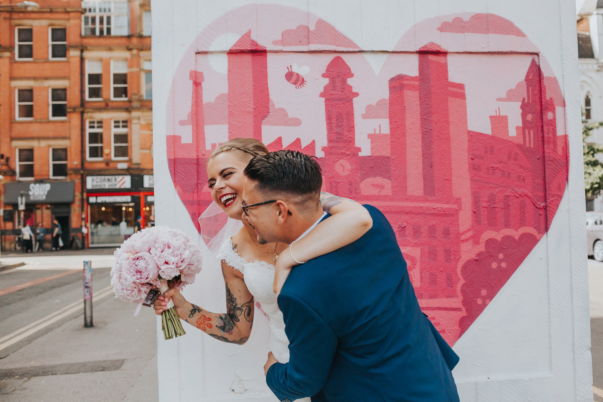 Couple laugh together in front of Manchester Graffiti.