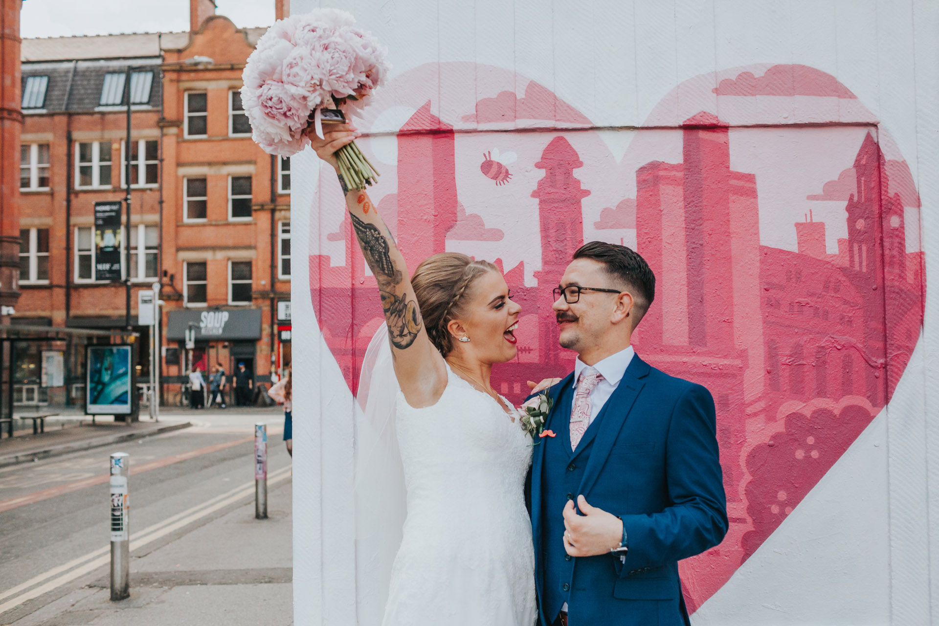 Bride holds flowers up cheering in Manchester's Northern Quarter.