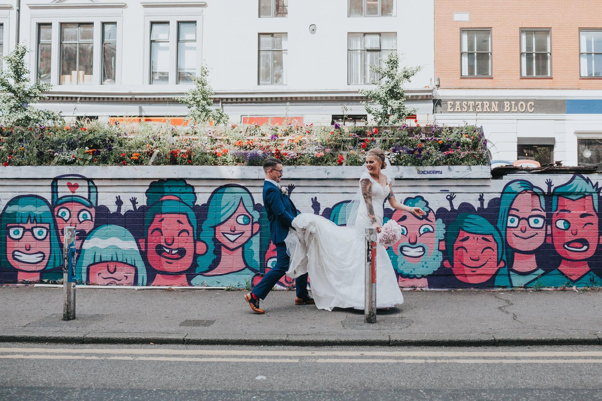 Groom holds brides dress for her as she walks past graffiti, Stevenson Square Manchester.