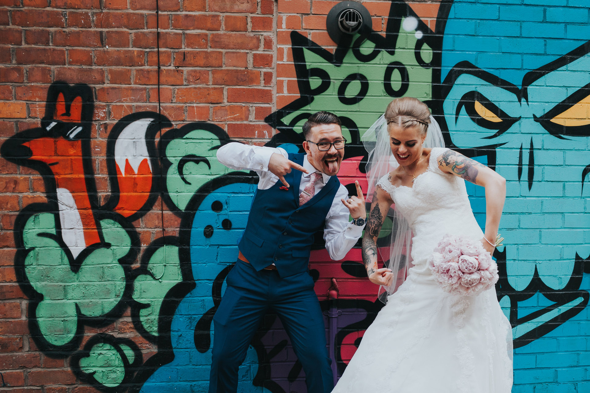 Bride and Groom pose in front of street art behind The Peer Hat, Manchester, Northern Quarter.