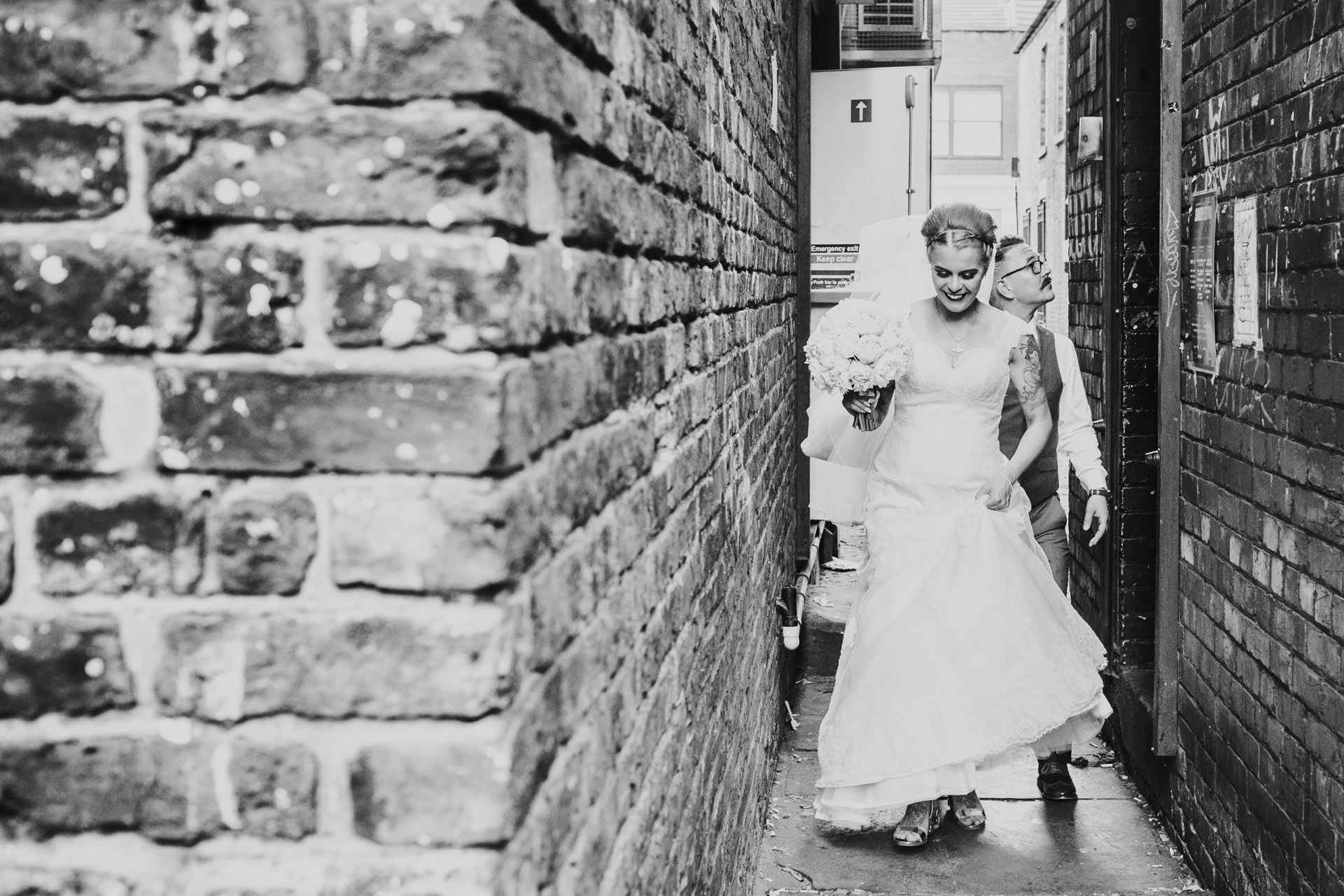 Bride walks down Manchester back alley with her wedding dress and flowers. Photograph in edited black and white.