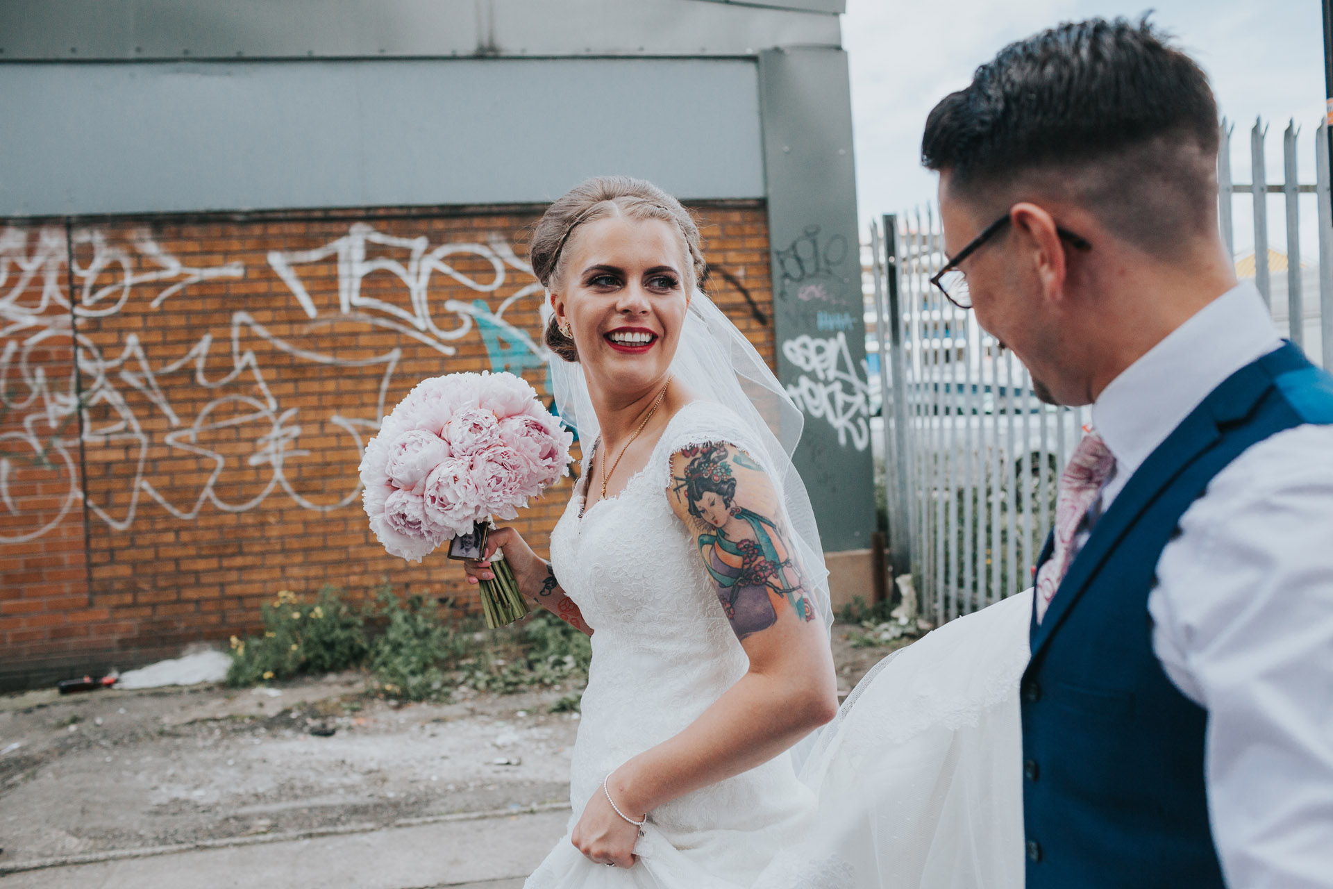 Bride looks to Groom as they walk through Manchester. Graffiti tags in back ground.