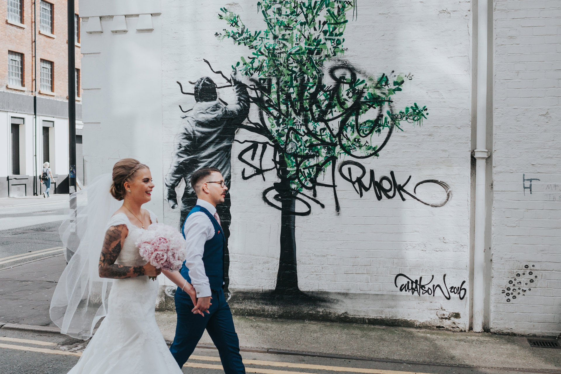 Bride and Groom walk past tree graffiti on Faraday Street, Manchester. Photograph processed in colour.