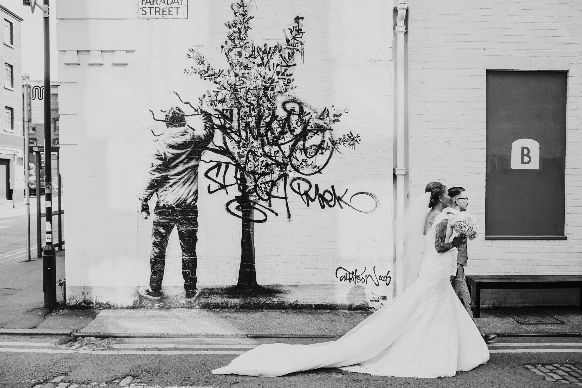 Photograph processed in black and white. Couple walk by Faraday Street, Tree Graffiti in Manchester.