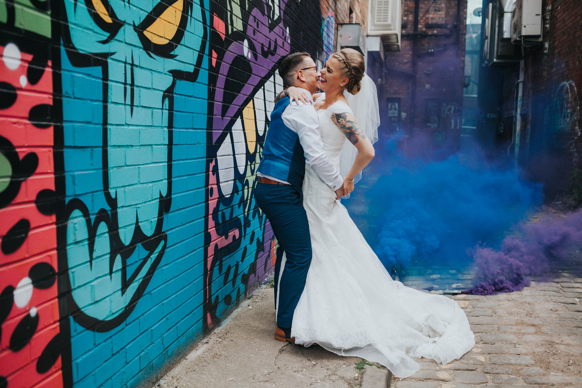 Bride and Groom in front o purple and blue street art with purple and blue smoke bombs, Northern Quarter, Manchester.
