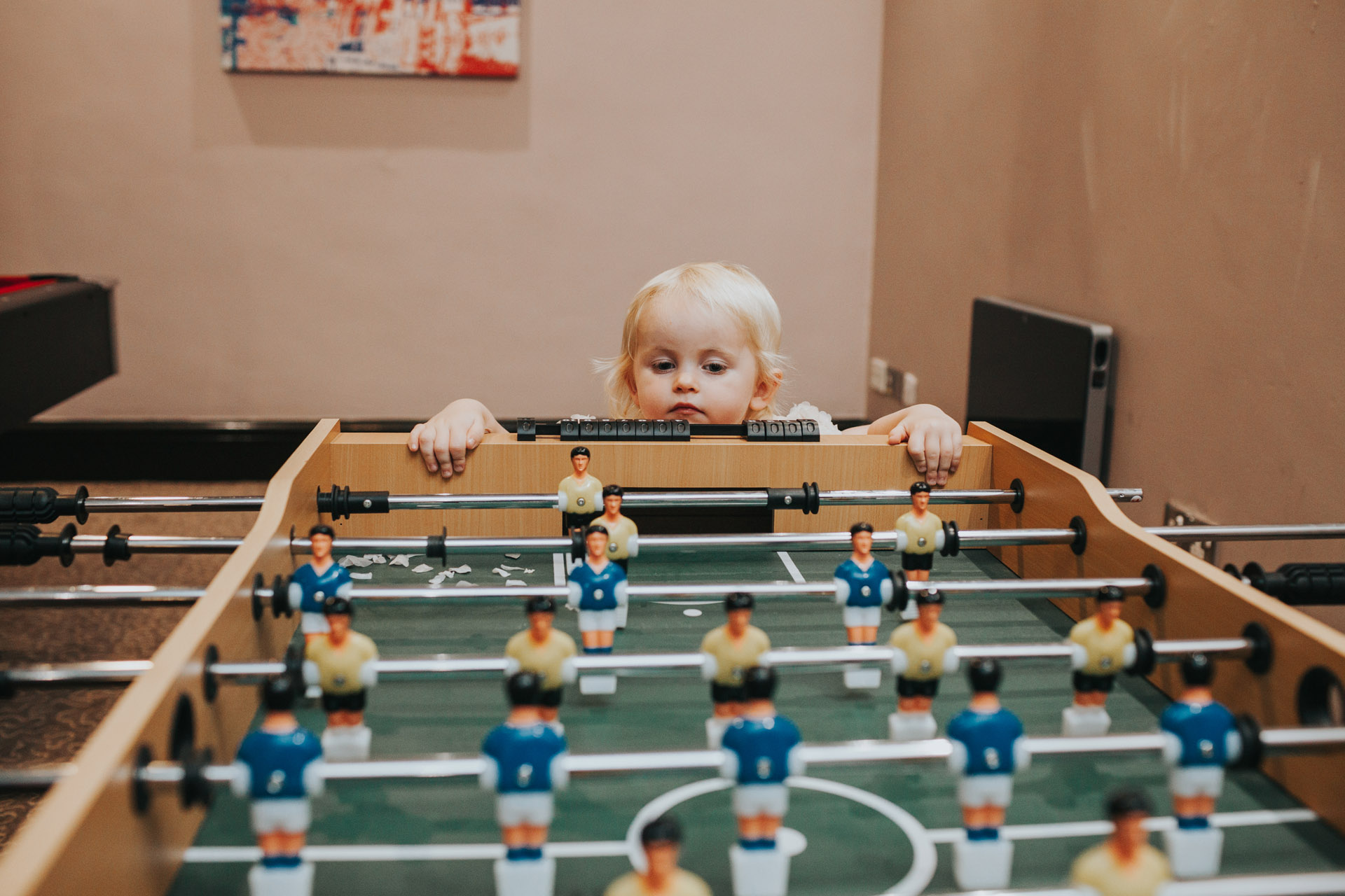 Toddler looking at table football.