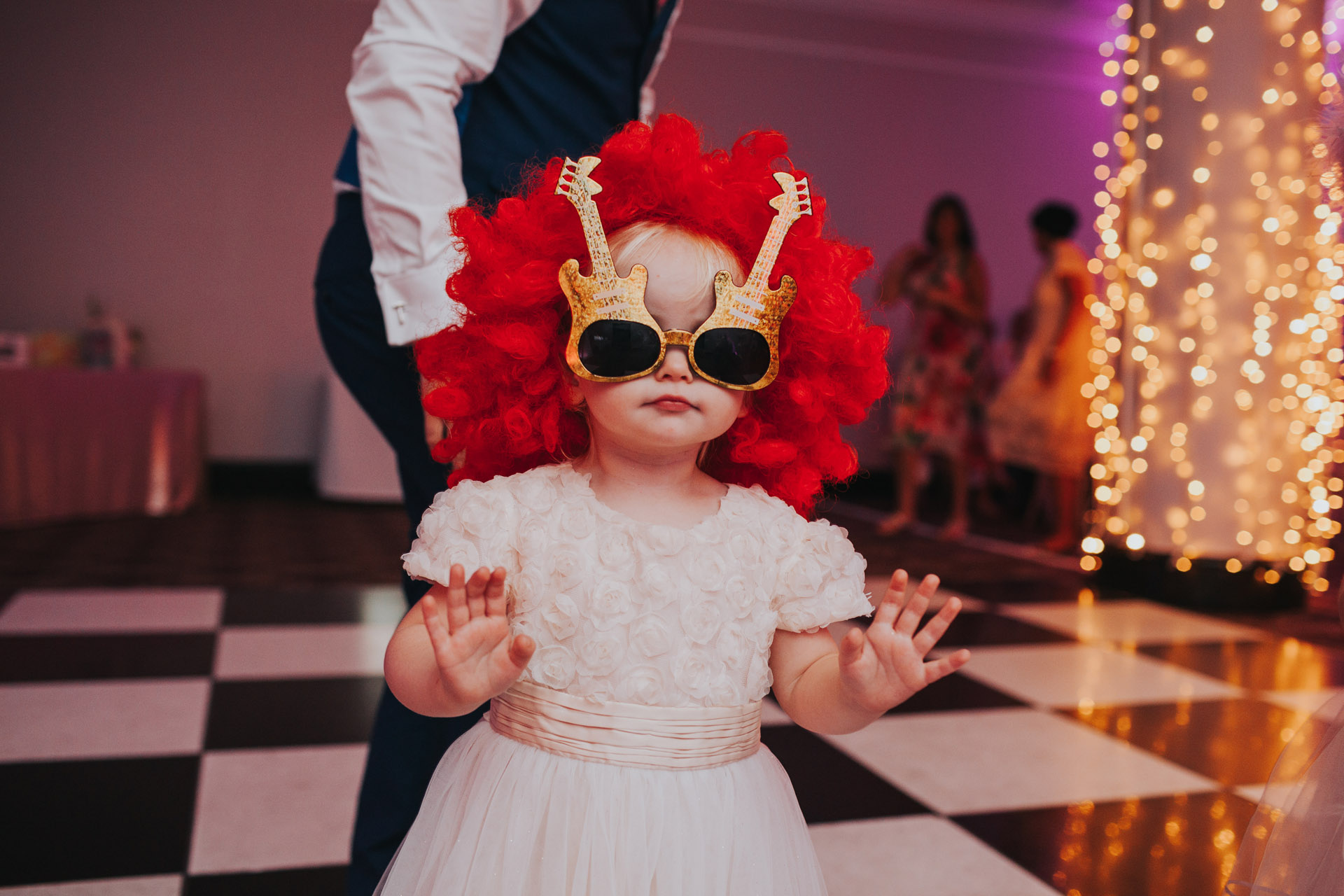 Toddler in wig and glasses on Manchester wedding dance floor.