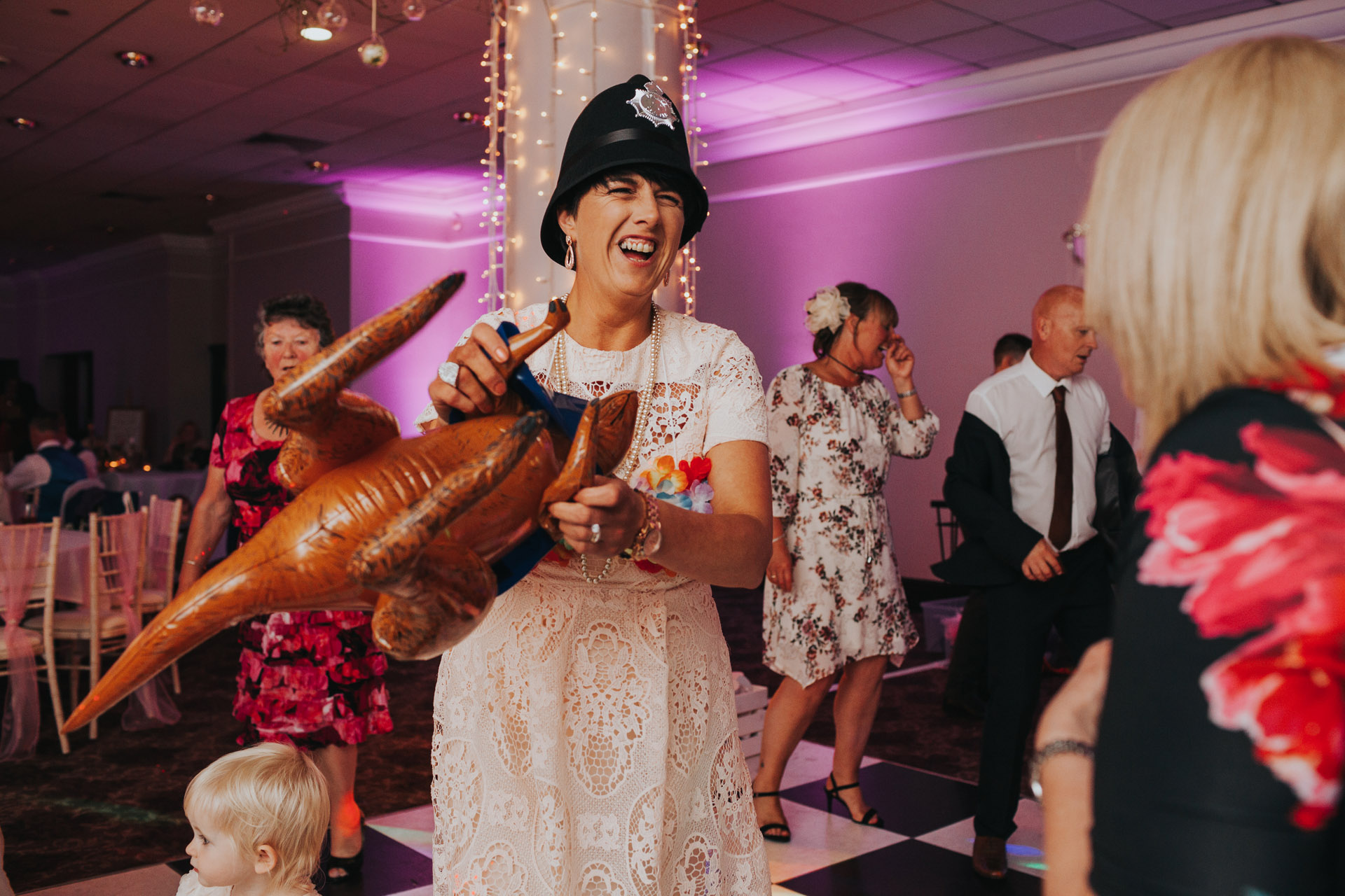 Wedding guest wearing a police helmet and holding a blow up dinosaur at Manchester Wedding.
