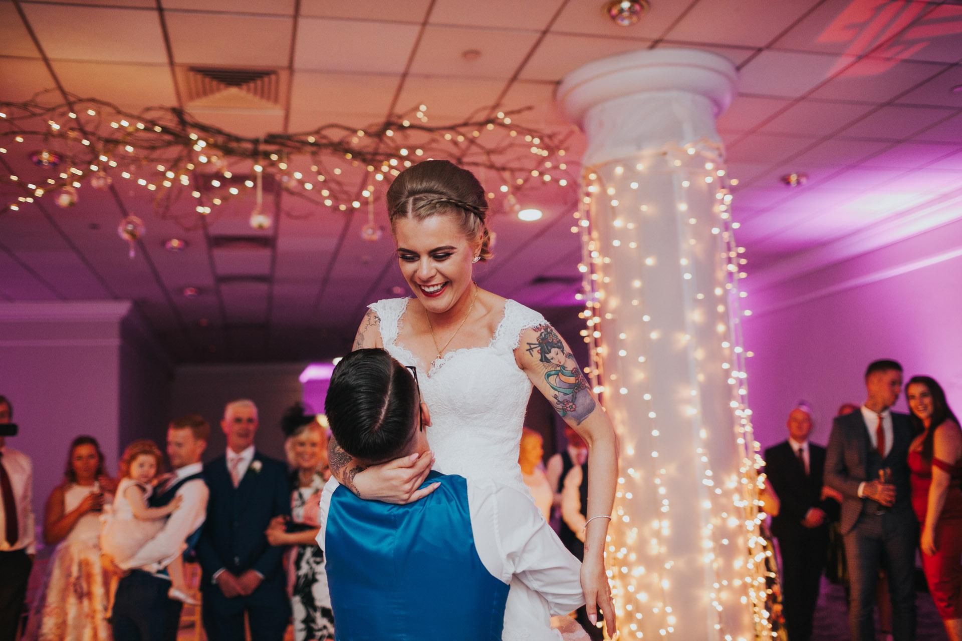 Groom lifts bride up on dance floor