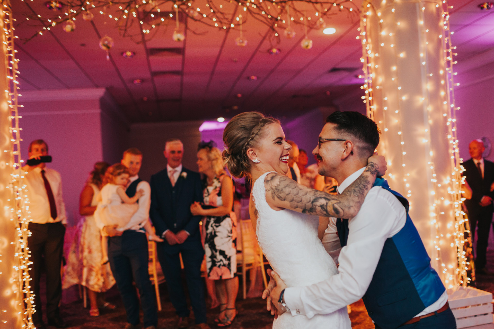 Bride and groom laugh together during first dance.