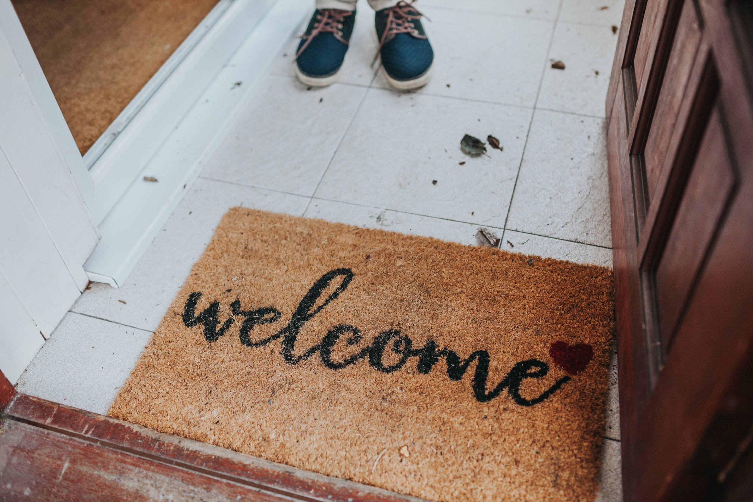 Welcome mat and feet at Evie's family home