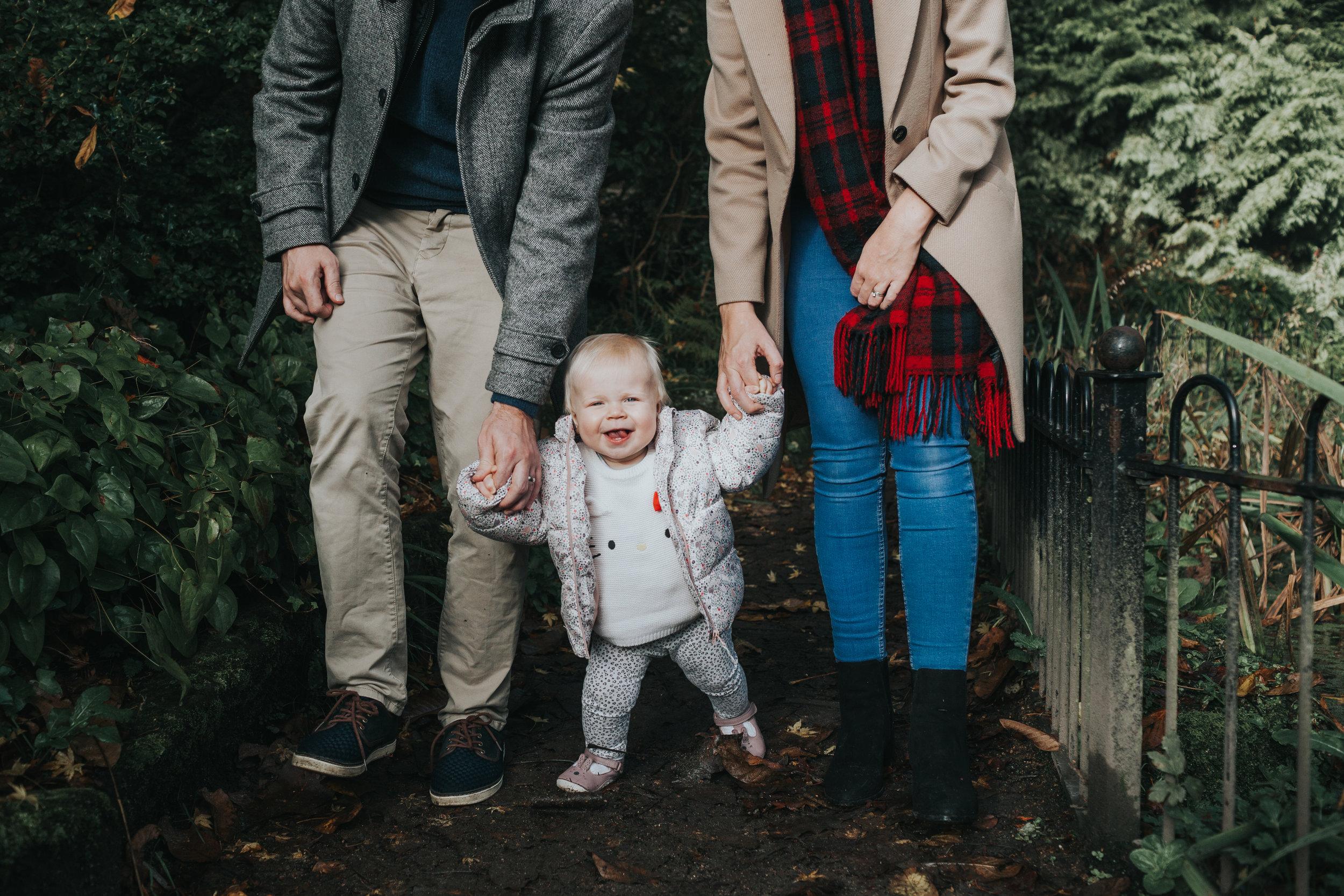 Evie is walking between her Mum and Dad's legs.