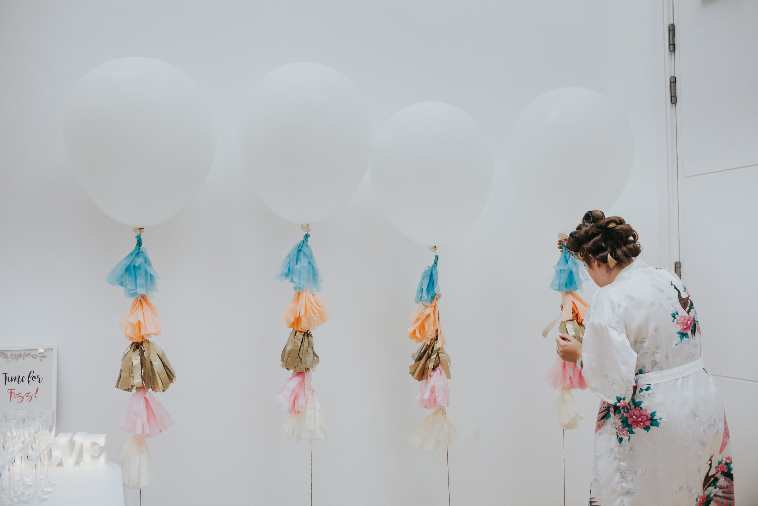 Bride in rollers dresses large white balloons on her wedding day in Liverpool.