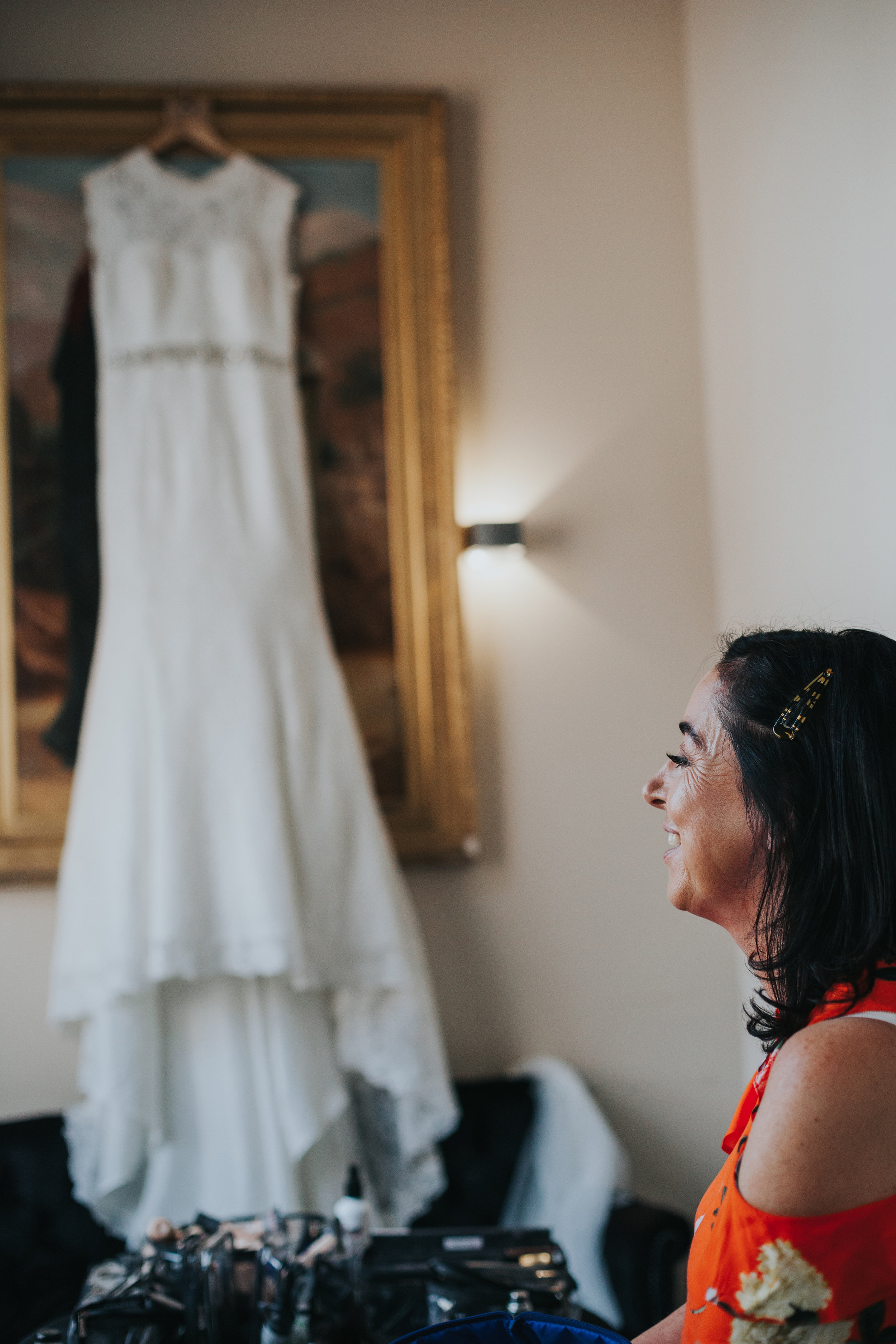 Brides mother stands in front of her wedding dress smiling.