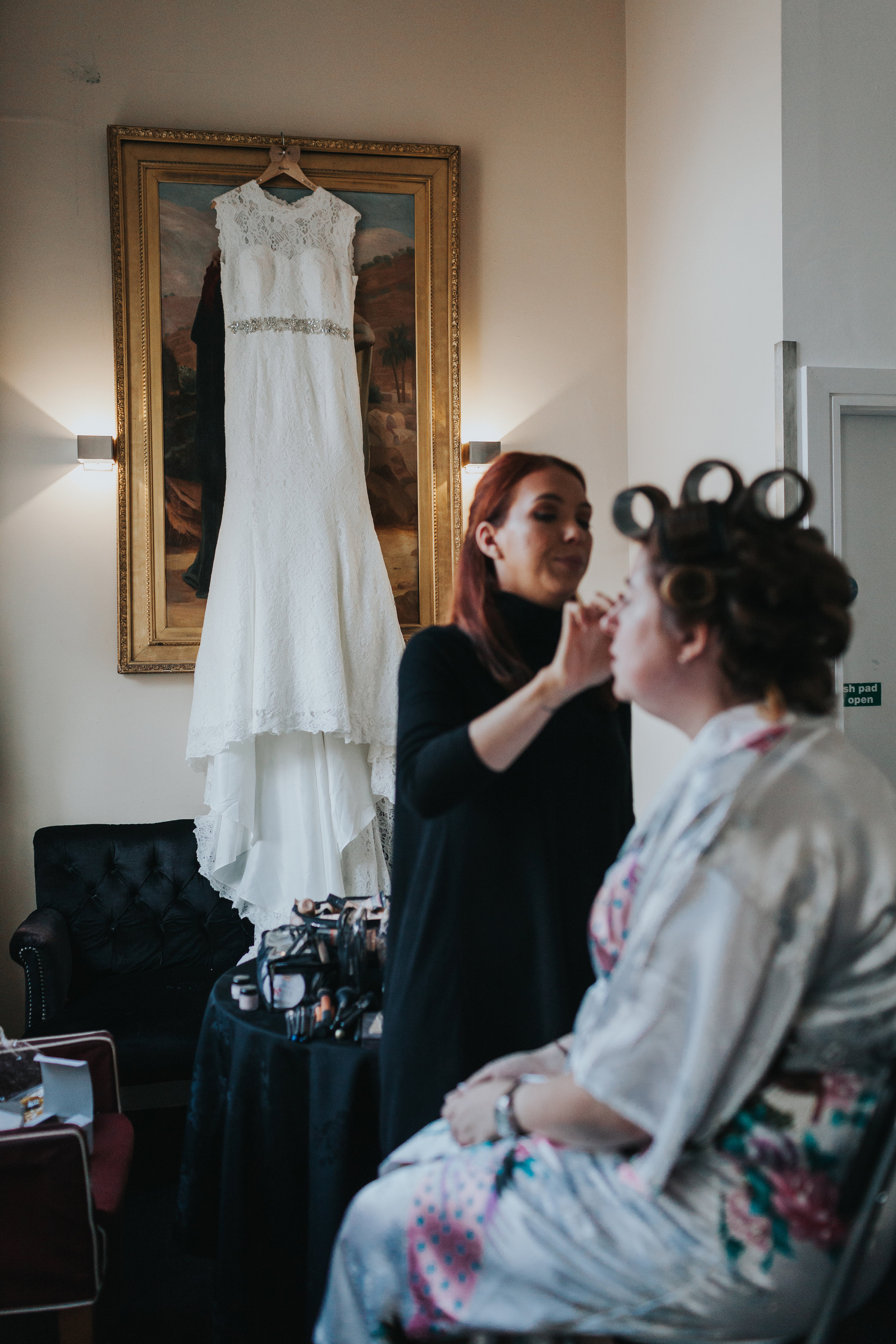 Bride in front of wedding dress getting her make up done.