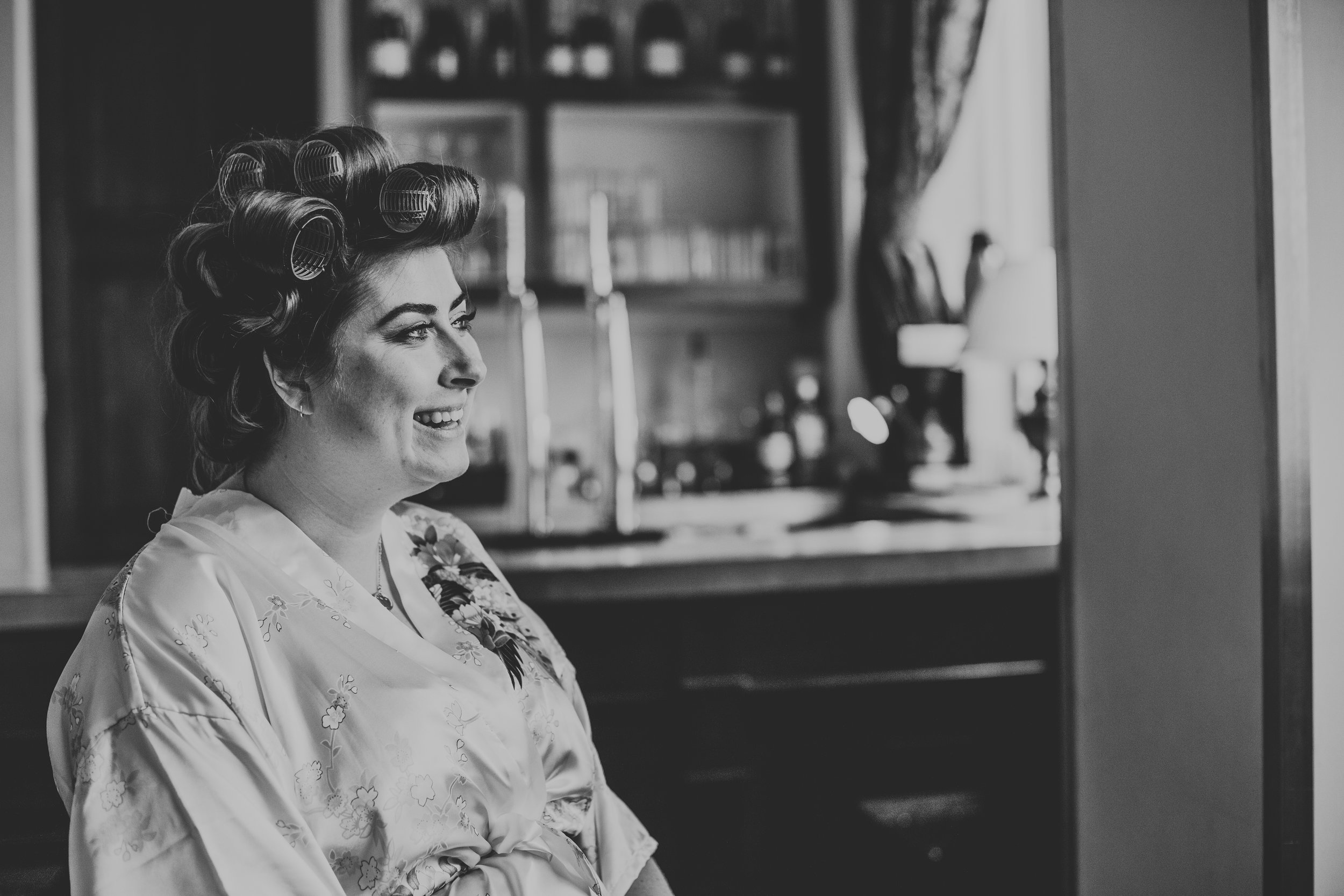 Bride smiling with her rollers in, in front of the bar.