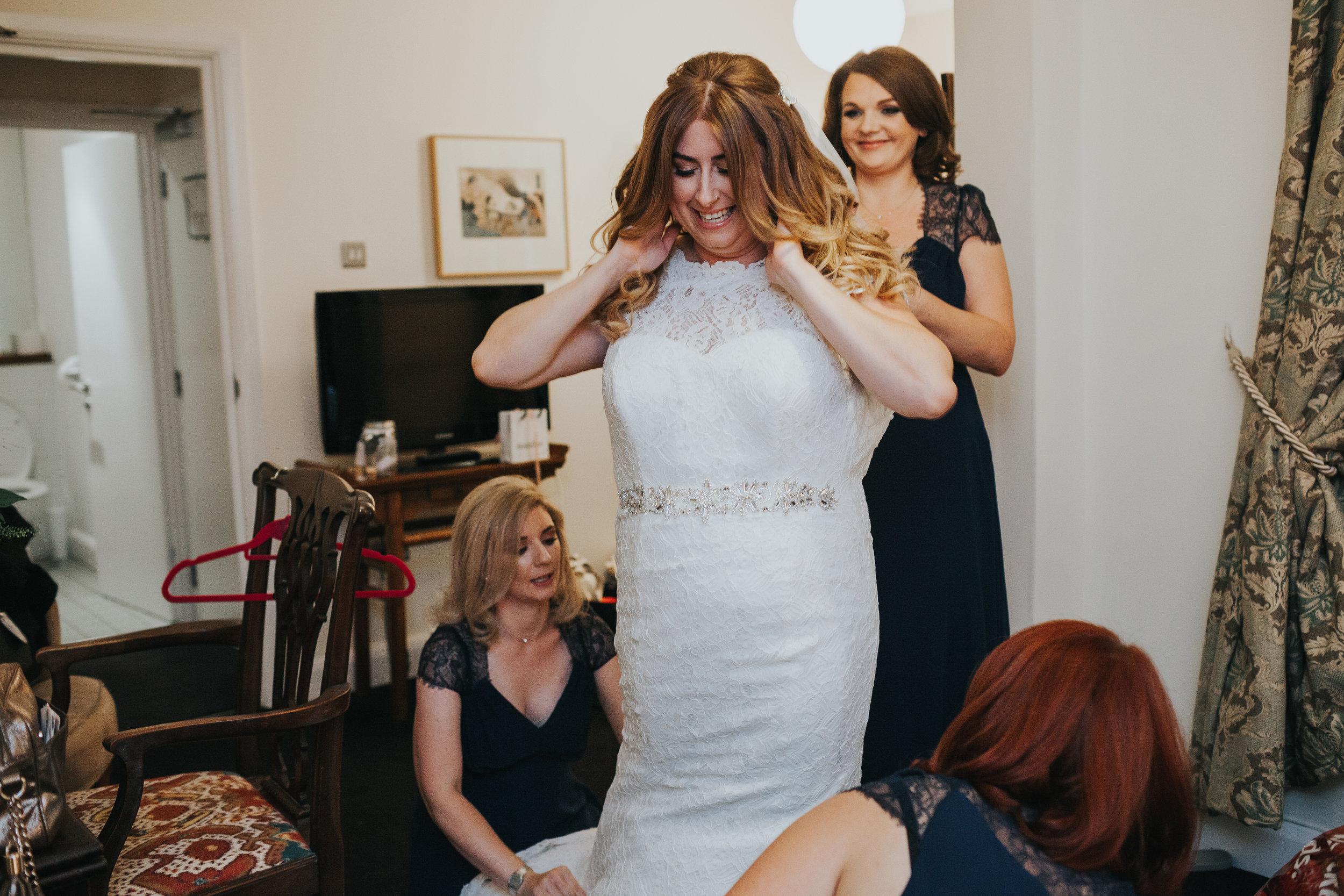 Bride gets into her wedding dress in her hotel room in merseyside.
