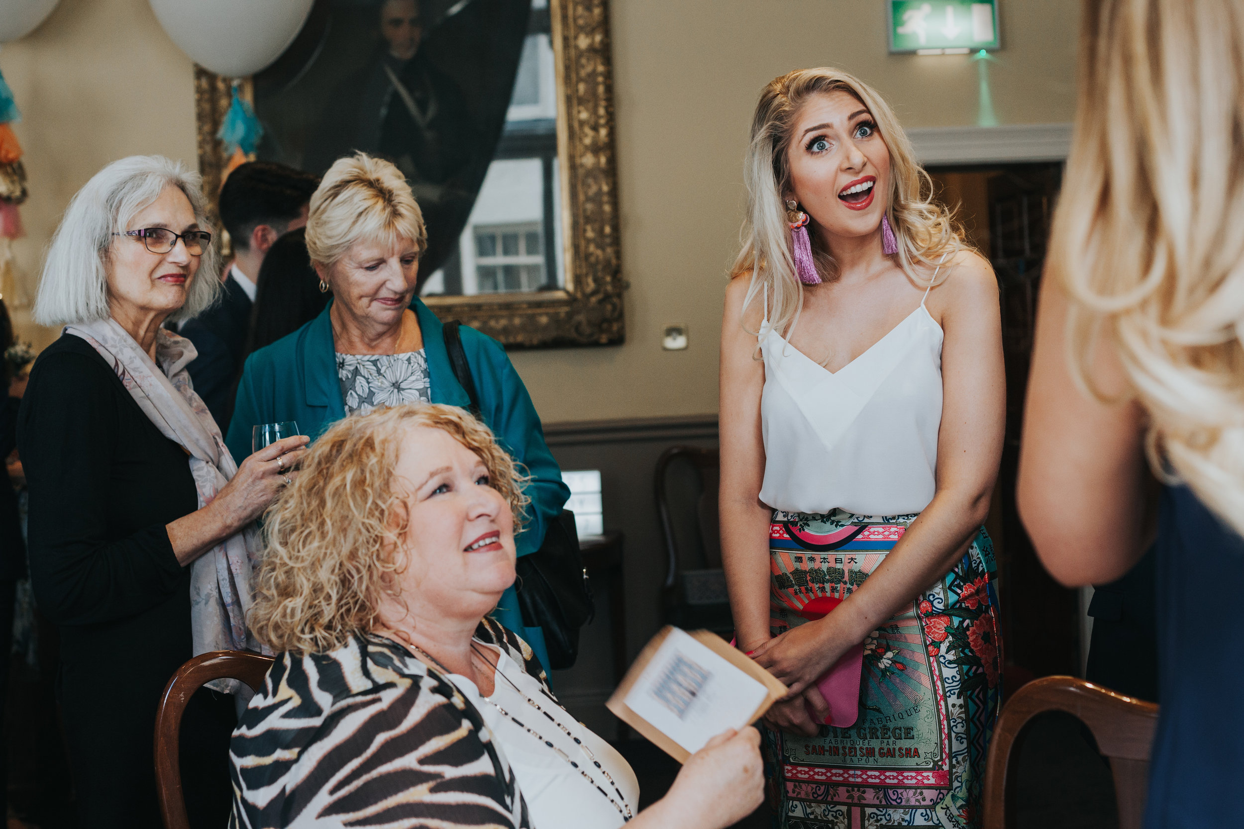 Wedding guests are catching up in the main hall room at The Racquet Club, Liverpool.
