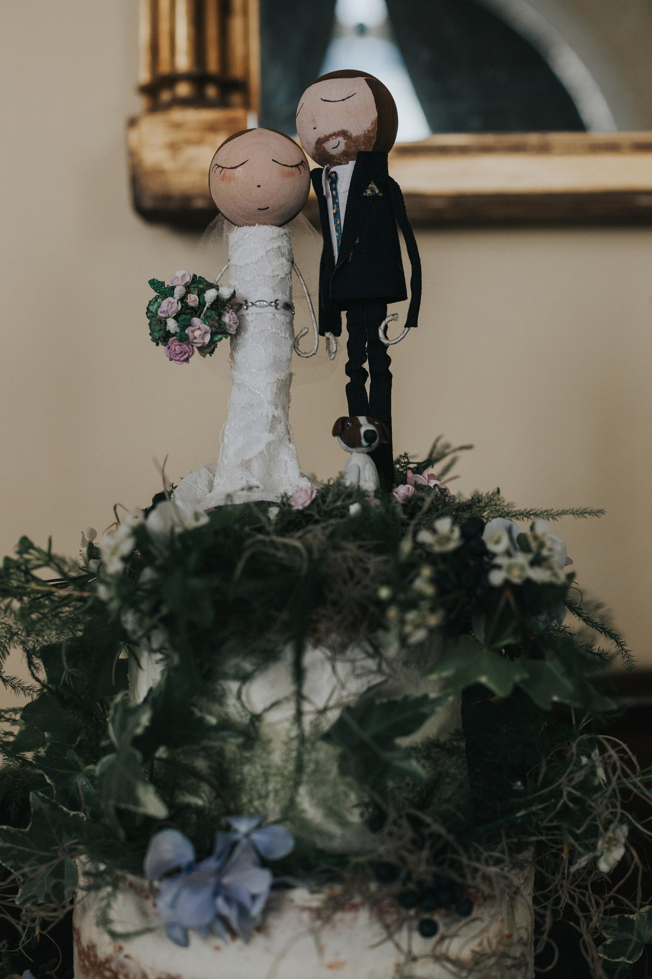 Bride and groom cake topper on wedding cake.