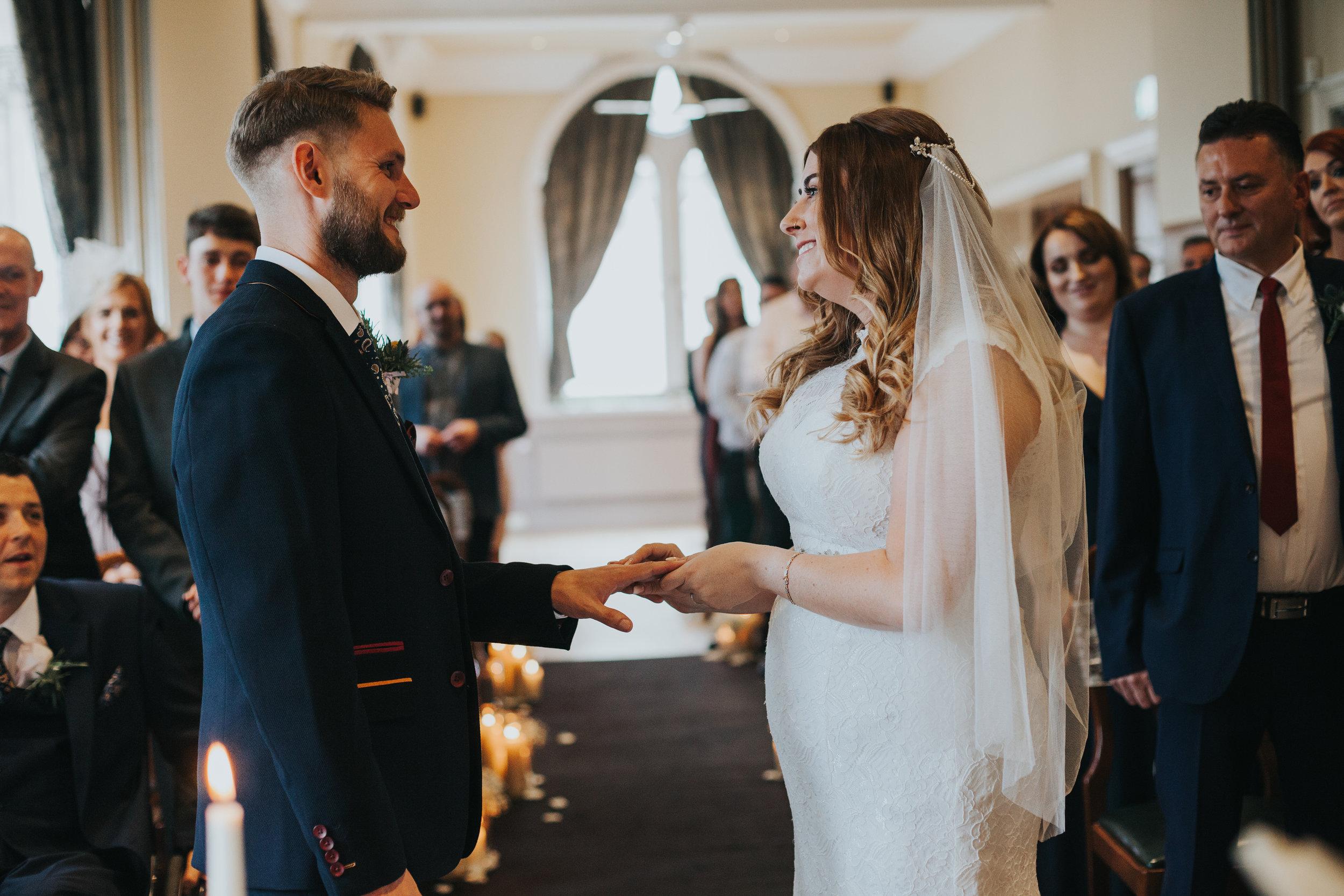 Bride and groom exchange wedding rings.