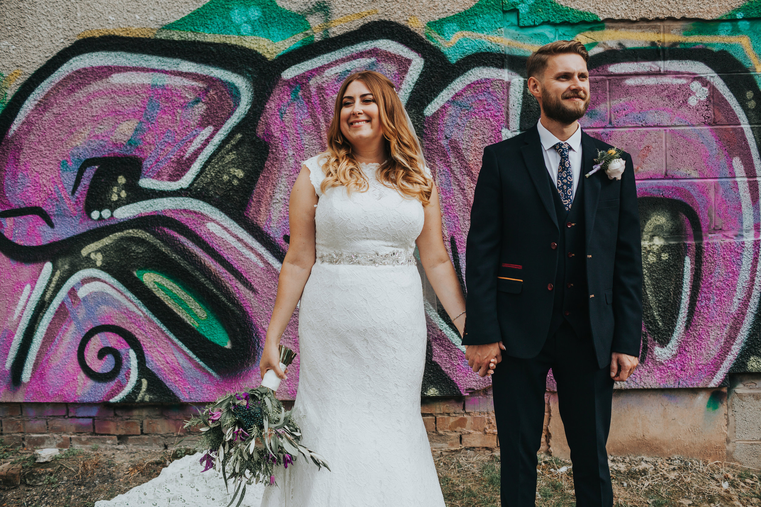 Bride and Groom stand in front of Graffiti.