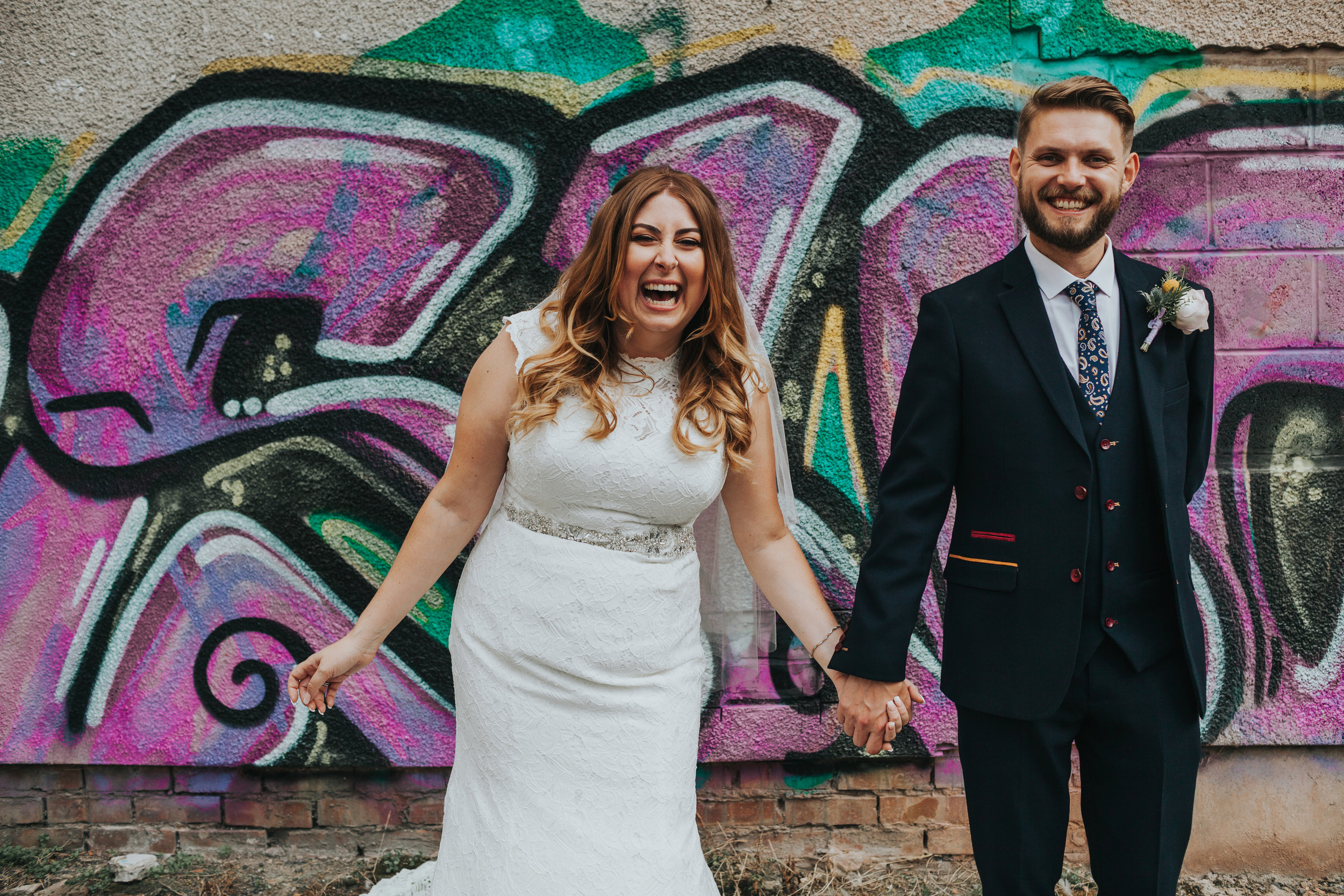 Bride and Groom Laugh in front street art in Liverpool.