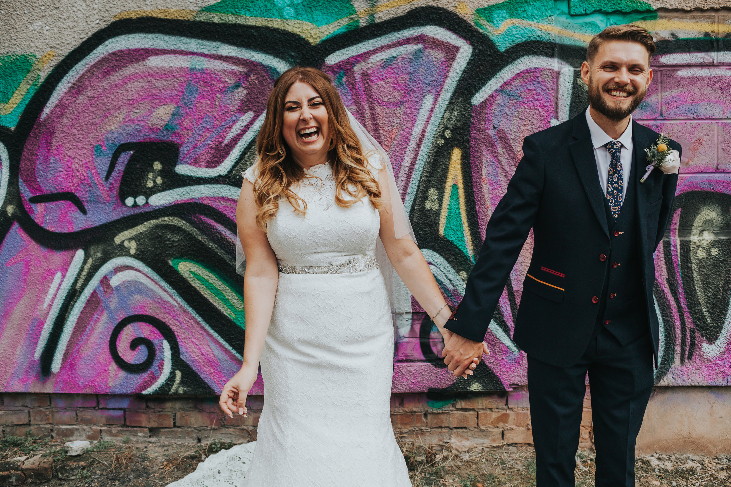 Bride and Groom in front of purple graffiti.