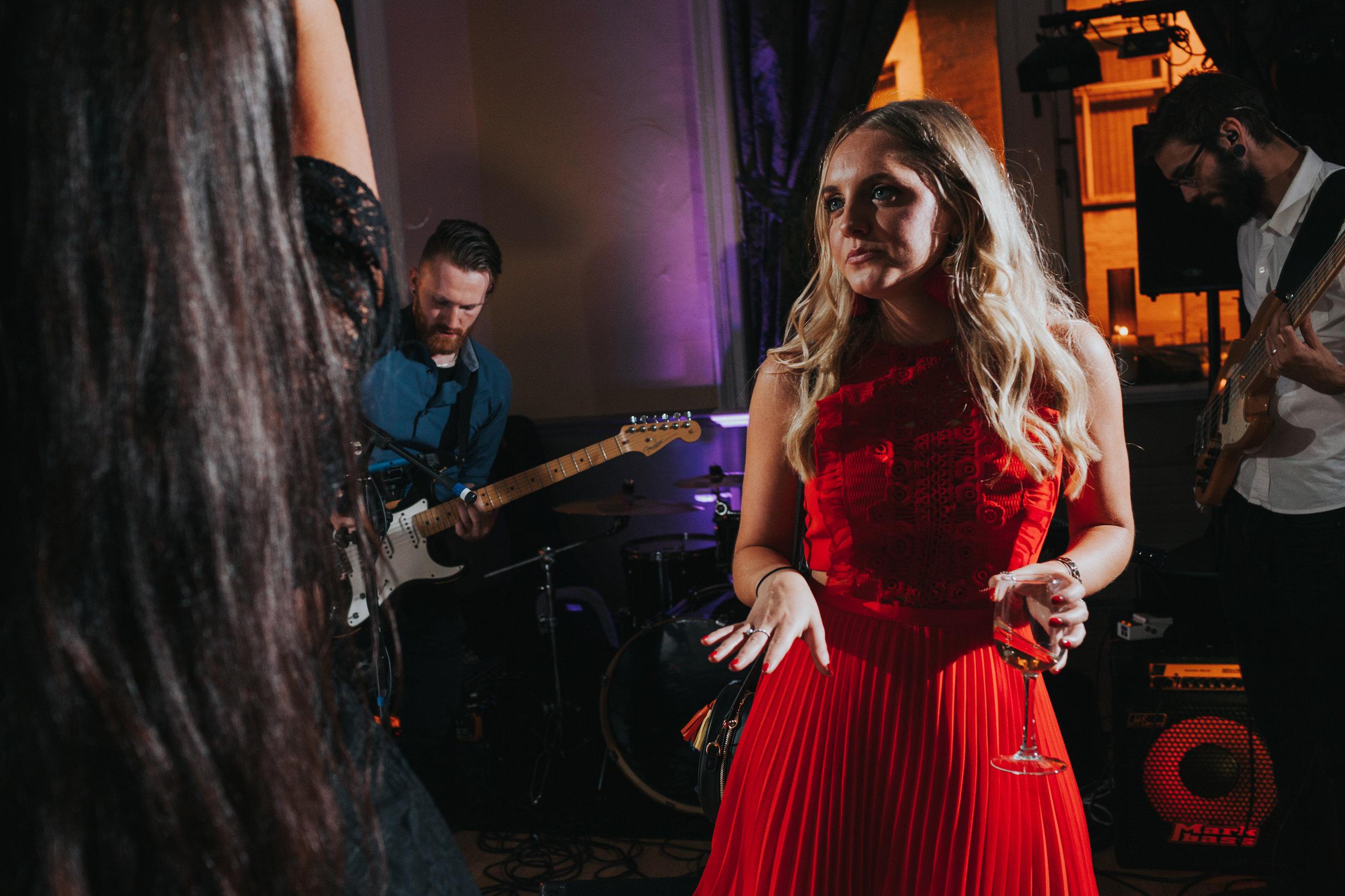 Wedding guest wearing red dress dancing.