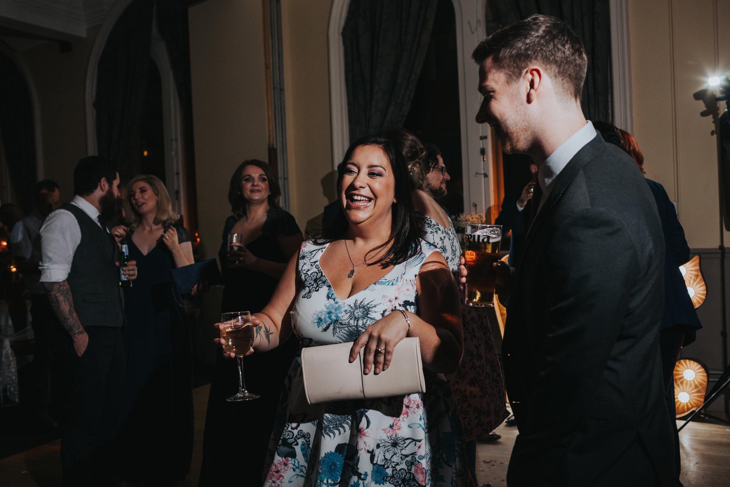 Wedding guests laugh together on dance floor.