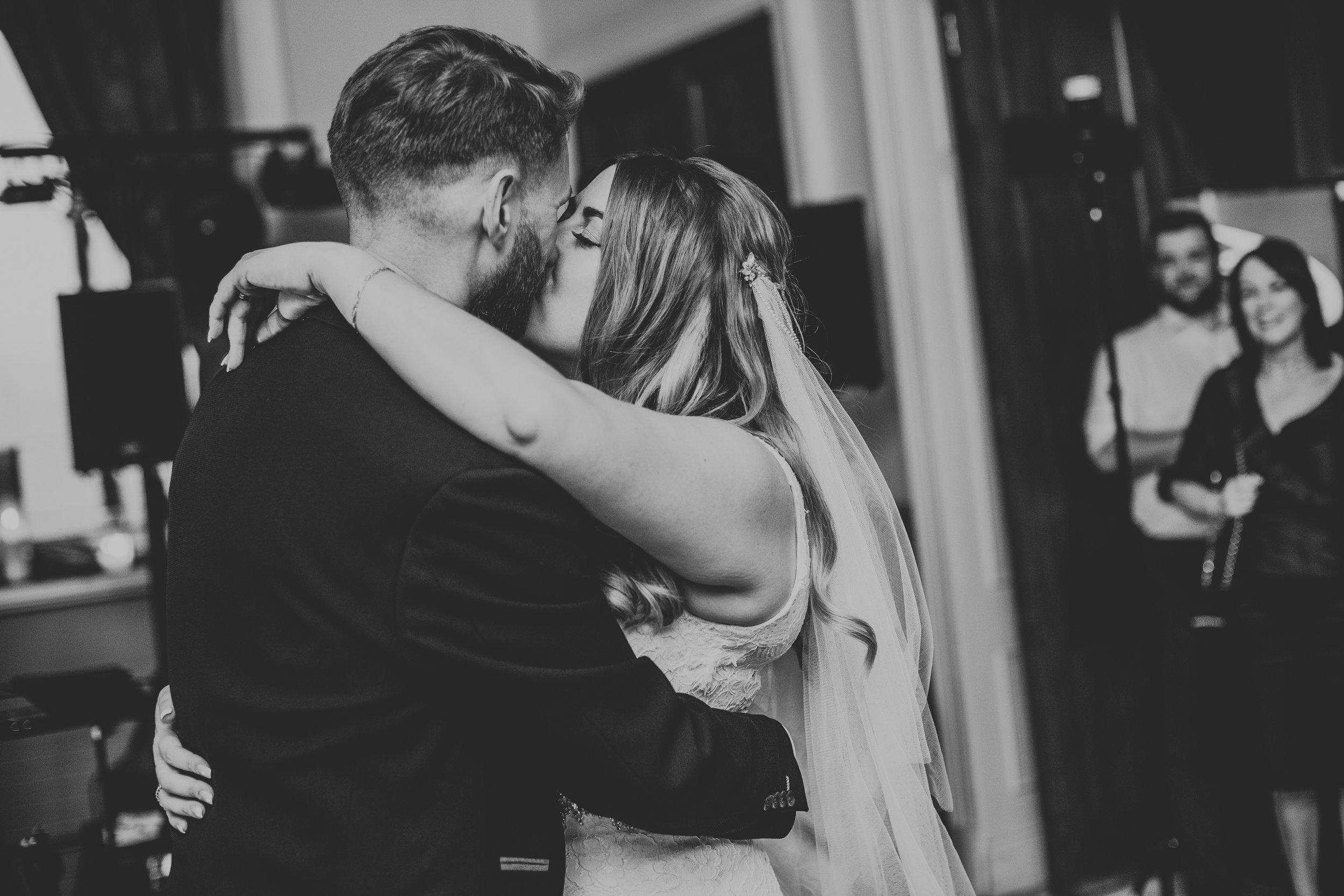 Bride and Groom kiss on dance floor.
