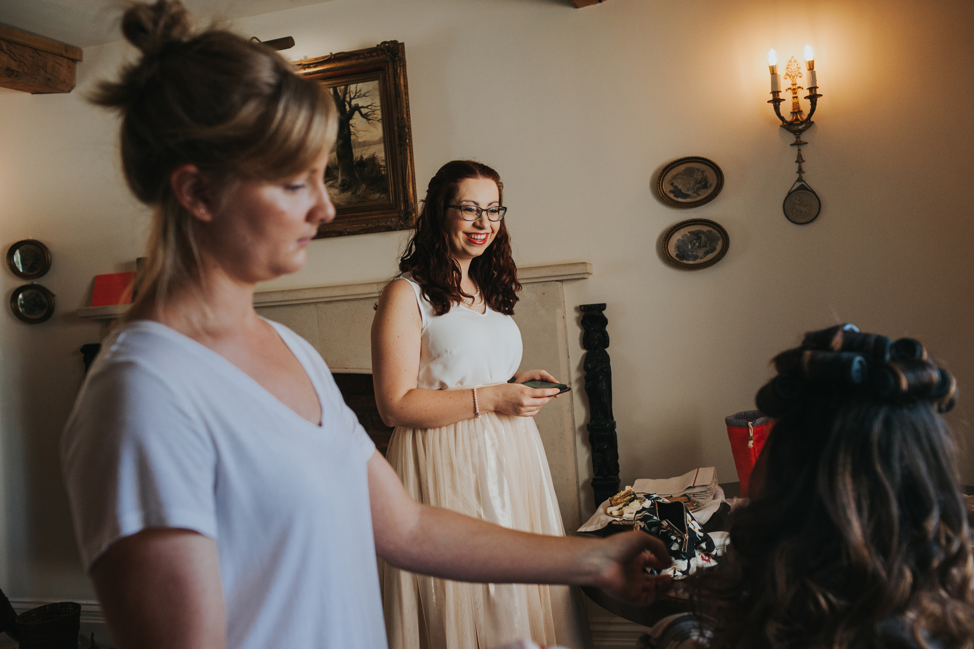 The bridesmaid looks on smiling as the bride has her finishing touches done.