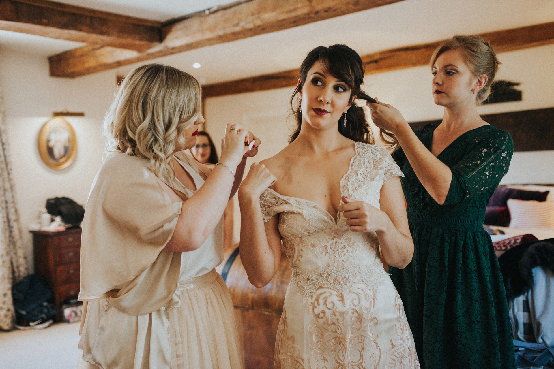 Bridesmaids fuss over Bride as she takes in the moment.