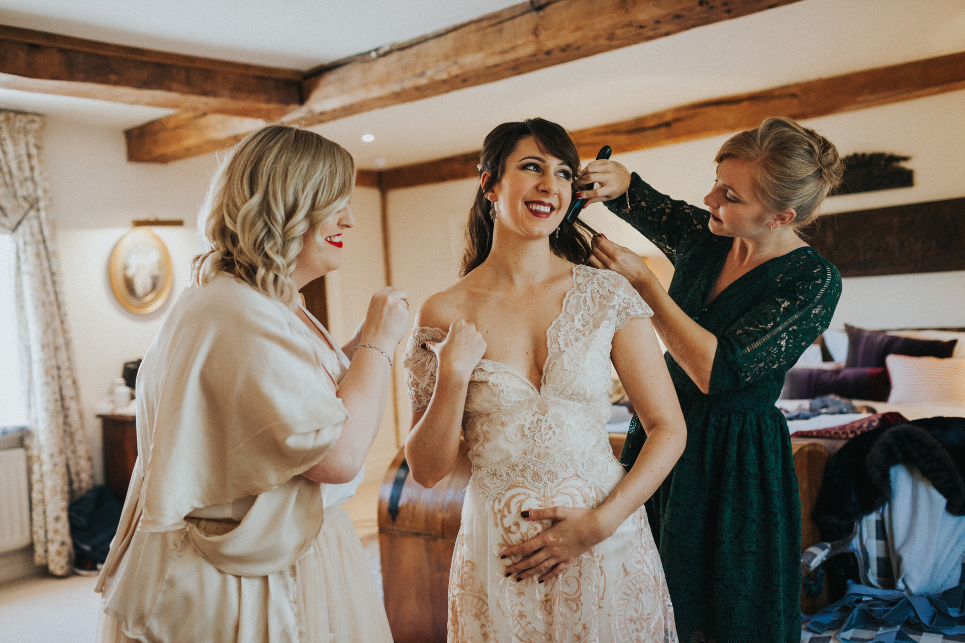 Bride laughing as bridesmaids and friends fuss over her.