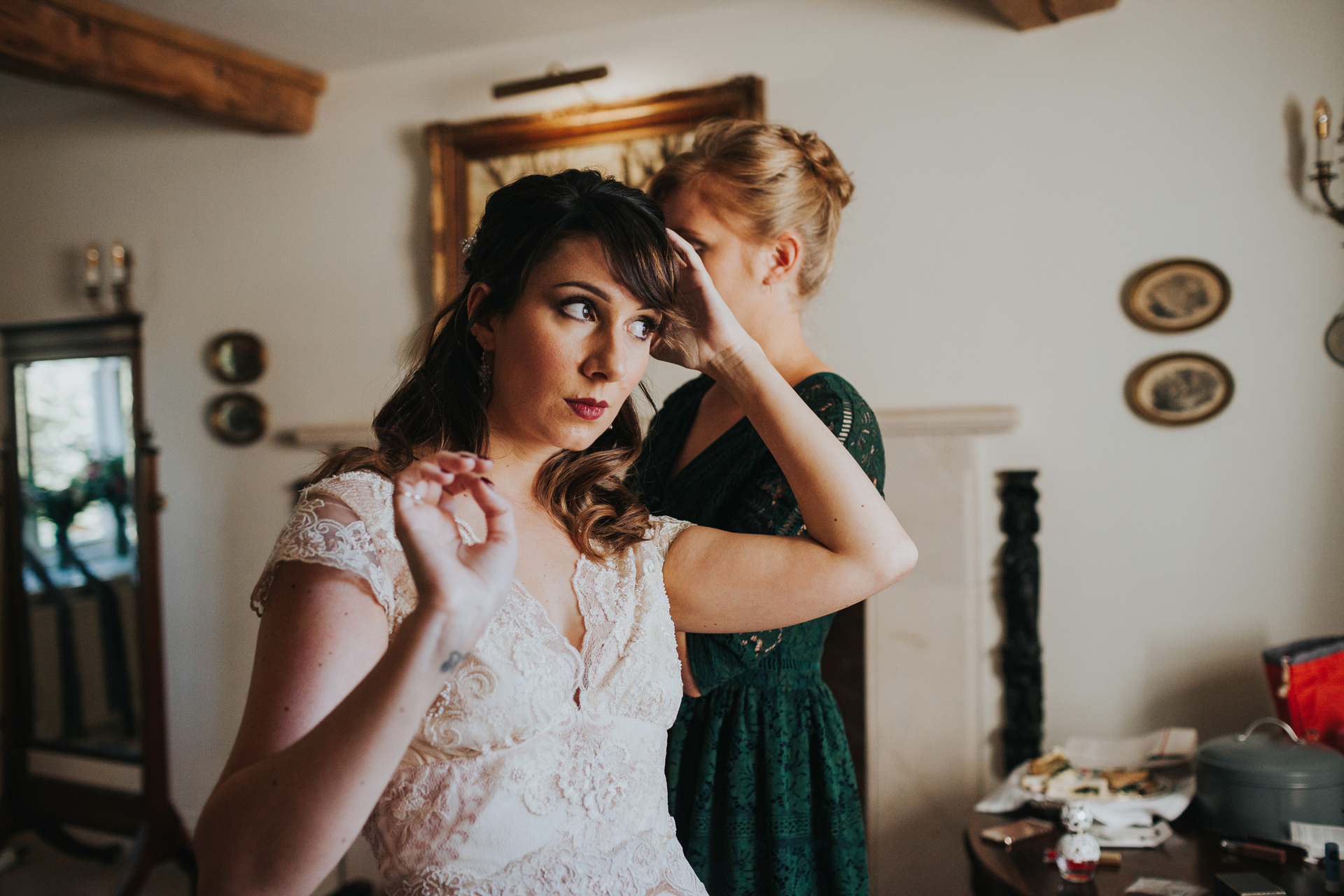 Bride checks out her hair in window light.