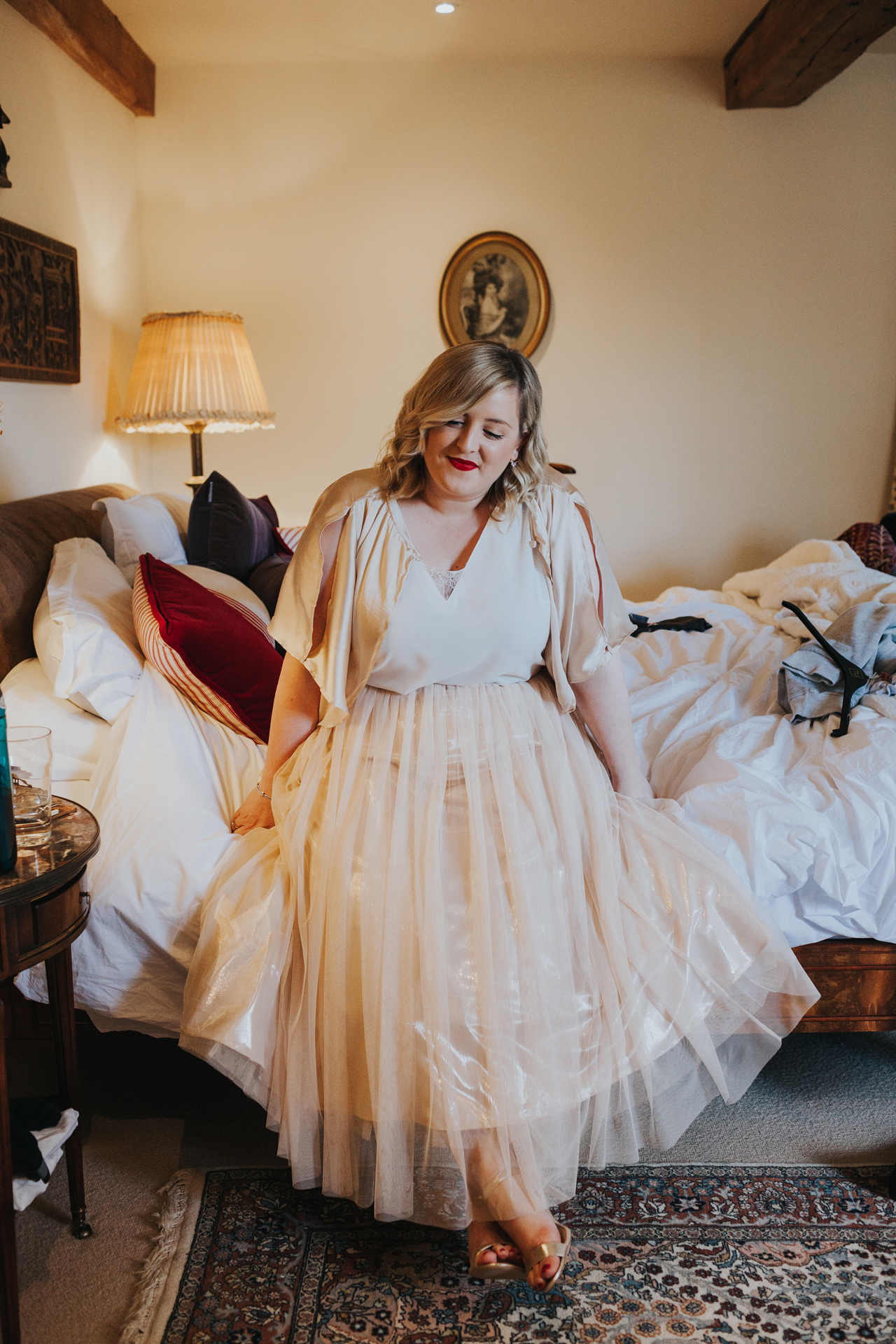 Bridesmaid sits on bed looking content with herself.
